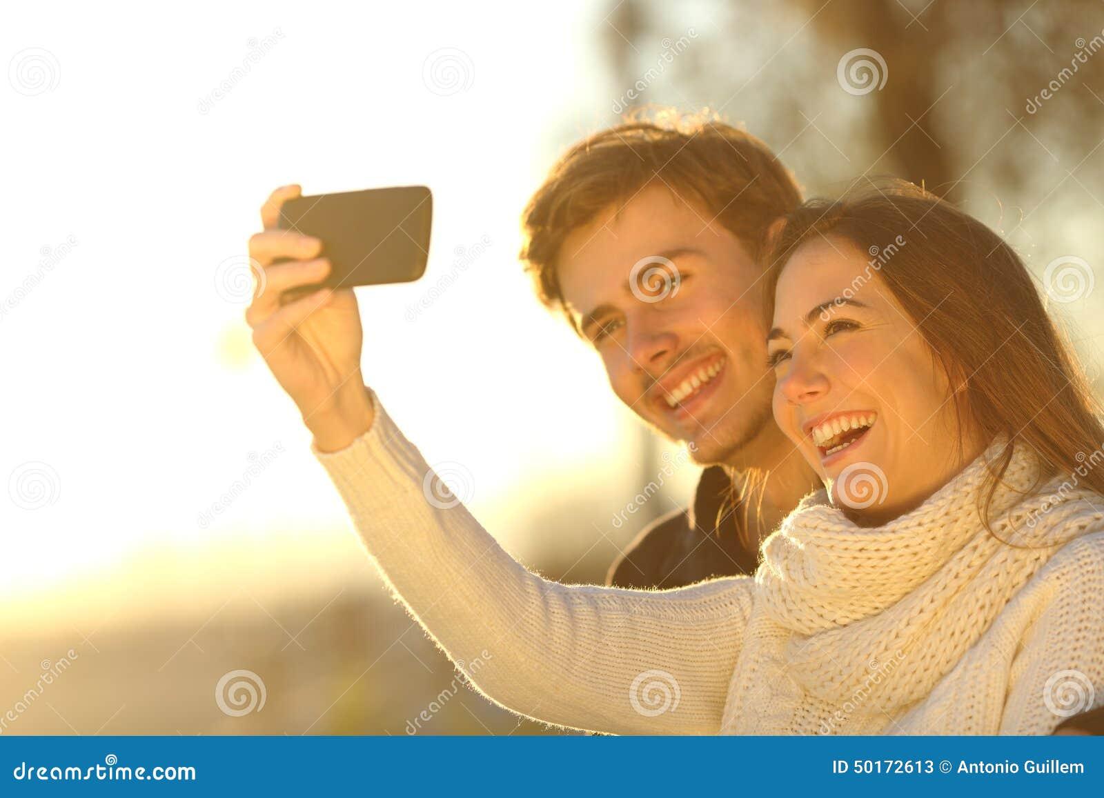 Dobiera się brać selfie fotografię z mądrze telefonem przy zmierzchem