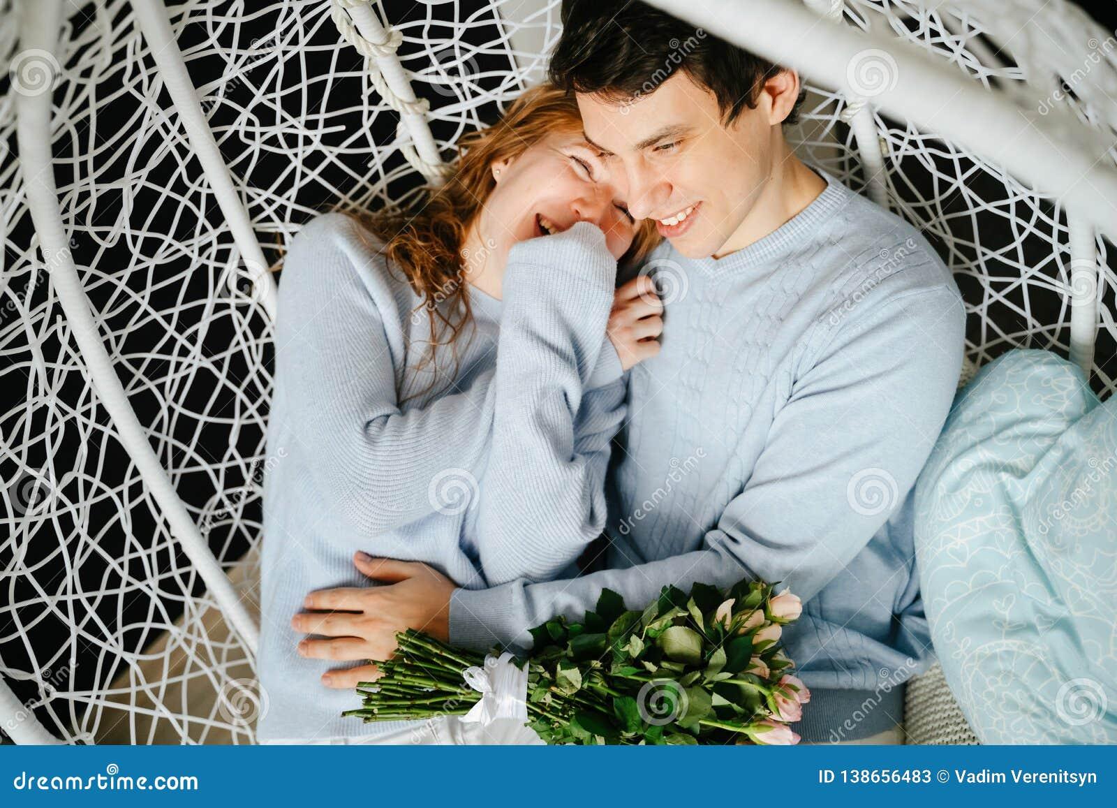 Dobiera się dziewczyny i faceta przytulenie na dużym krześle z bukietem róże