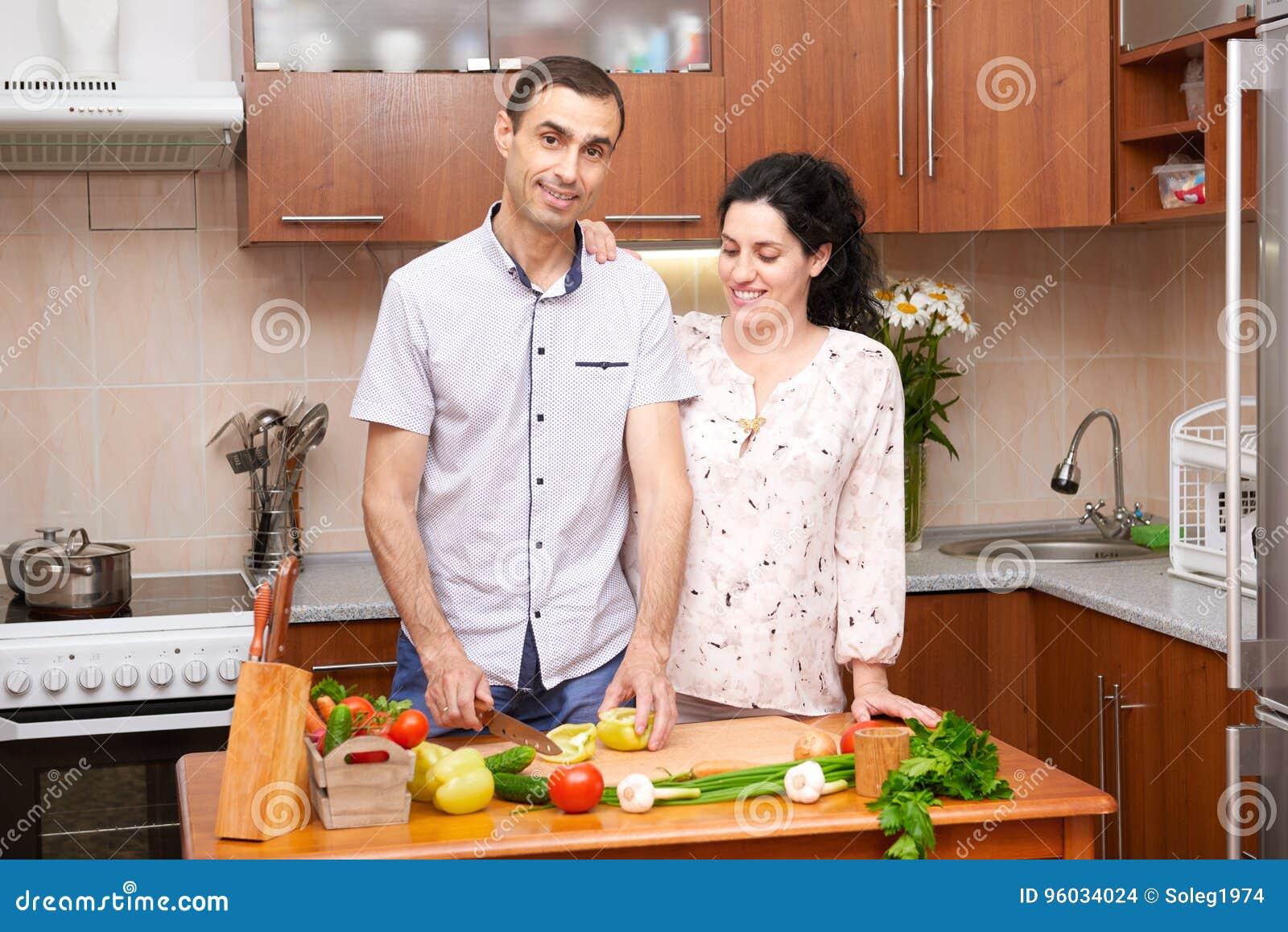 Dobiera się kucharstwo w kuchennym wnętrzu z świeżymi owoc i warzywo, zdrowym karmowym pojęciem, kobieta w ciąży i mężczyzna,