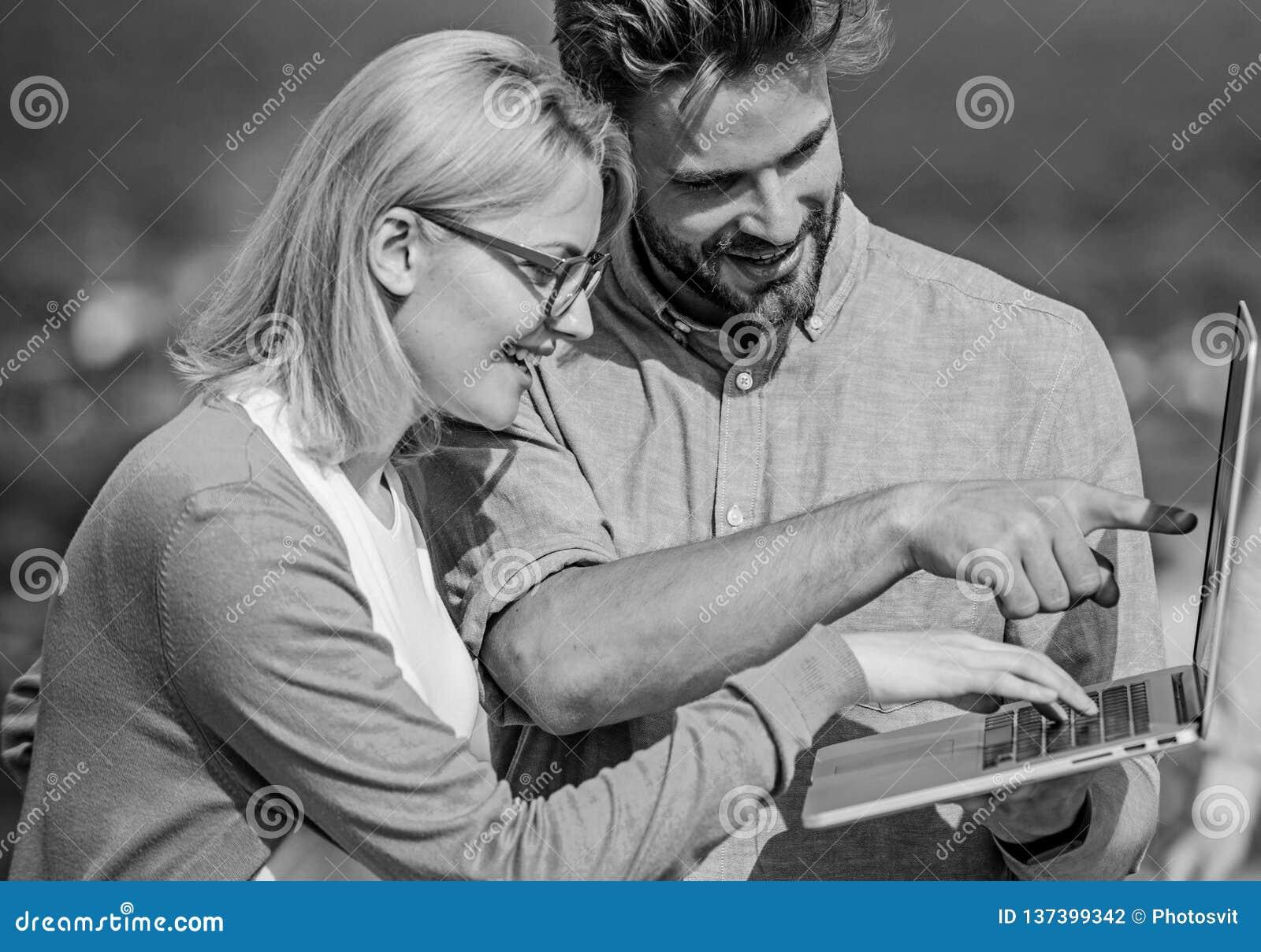 Dobiera się pracującego laptopu plenerowego słonecznego dzień, natury tło Mężczyzna i dziewczyna ciekawiący informacja ekranu not