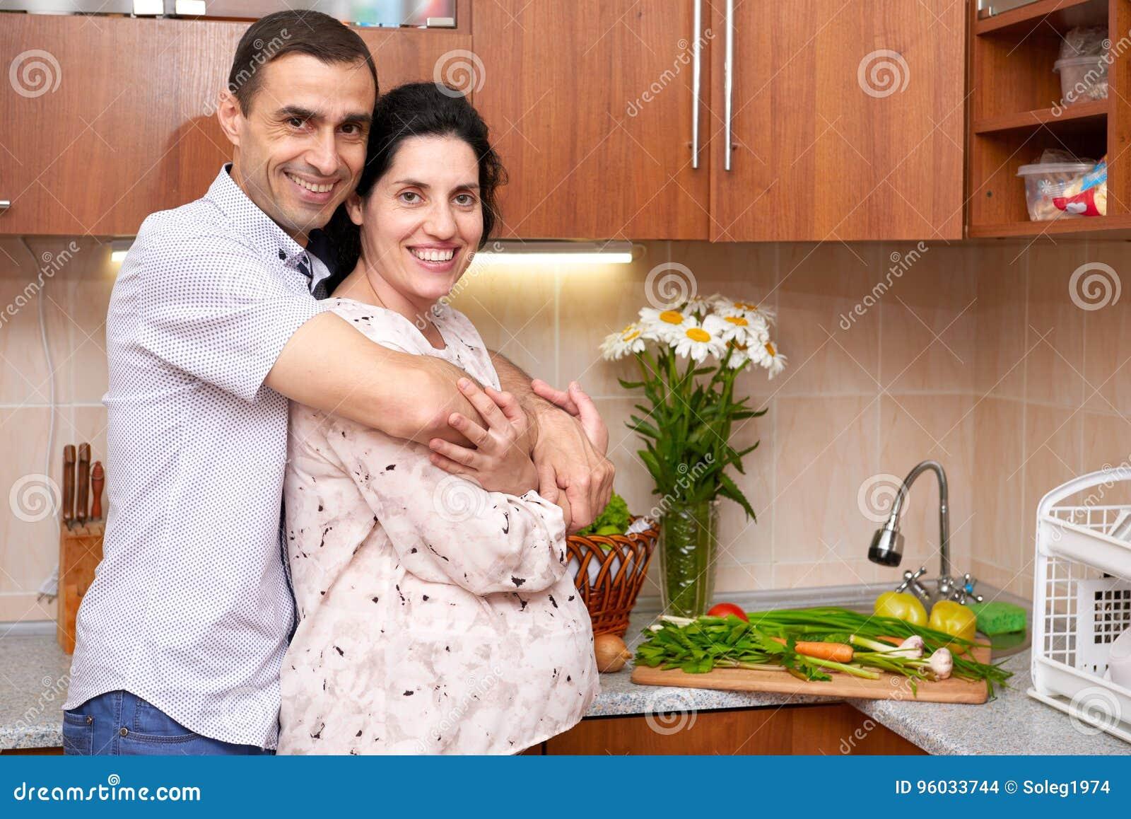 Dobiera się w kuchennym wnętrzu z świeżymi owoc i warzywo, zdrowym karmowym pojęciem, kobieta w ciąży i mężczyzna,