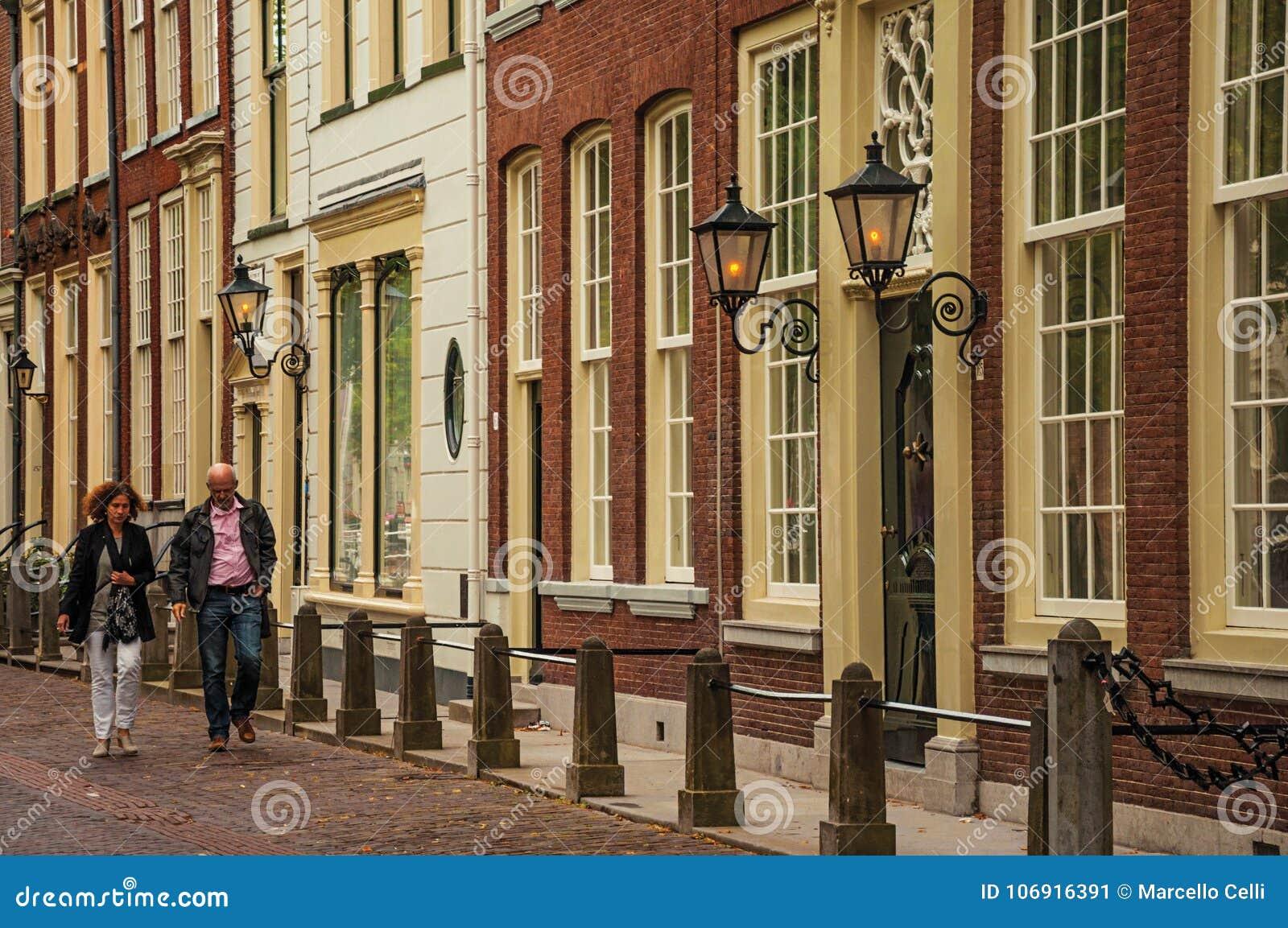 Dobiera się odprowadzenie na ulicie z eleganckimi semidetached ceglanymi domami na chmurnym dniu w Delft