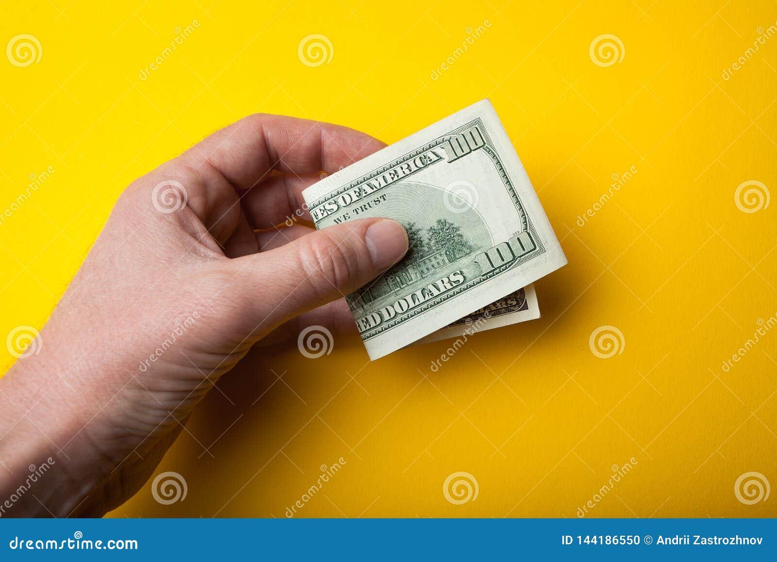 Doblado cientos billetes de dólar a disposición en un fondo, una venta o una compra amarilla