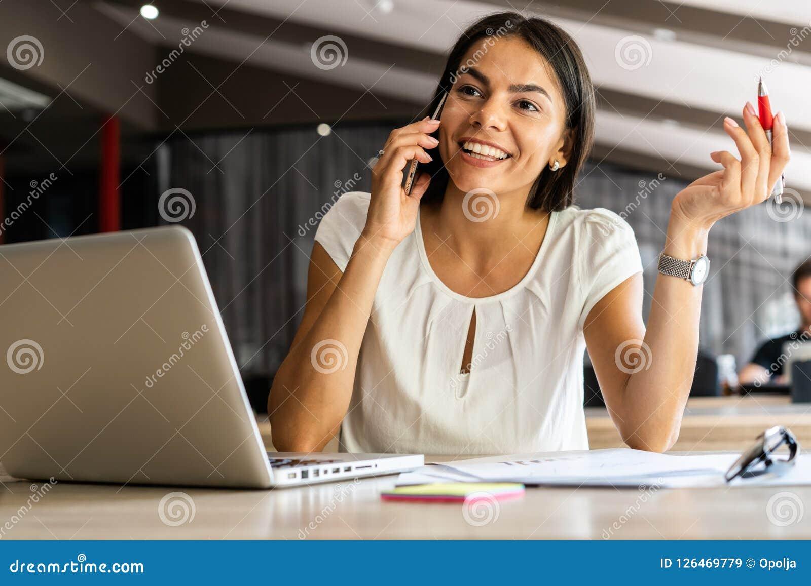 Dobra biznesowa rozmowa Rozochocona młoda piękna kobieta opowiada na telefonie komórkowym i używa laptop z uśmiechem przy podczas