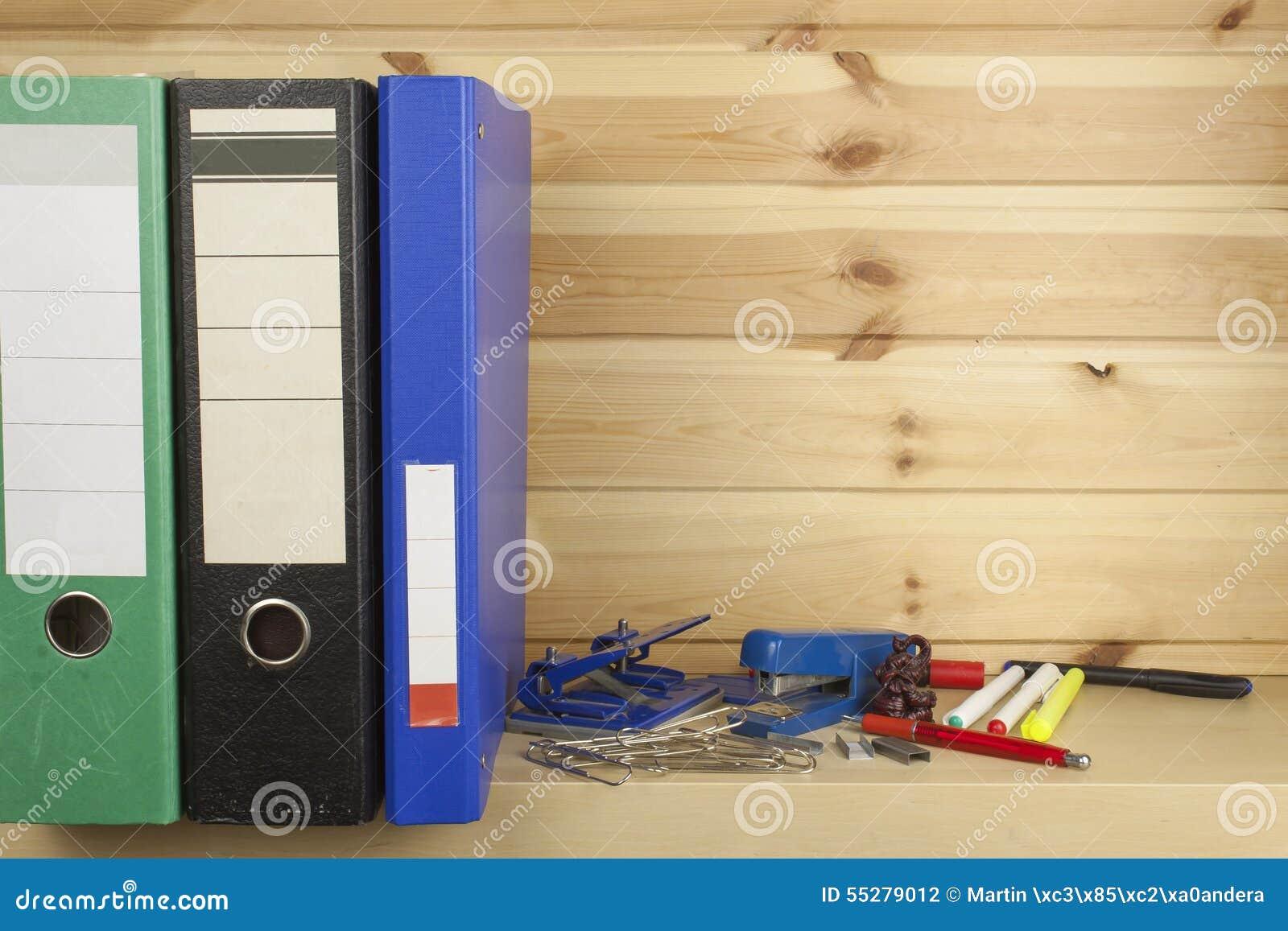 Dobradores, grampeadores e perfuradores de furo que encontram-se em uma prateleira