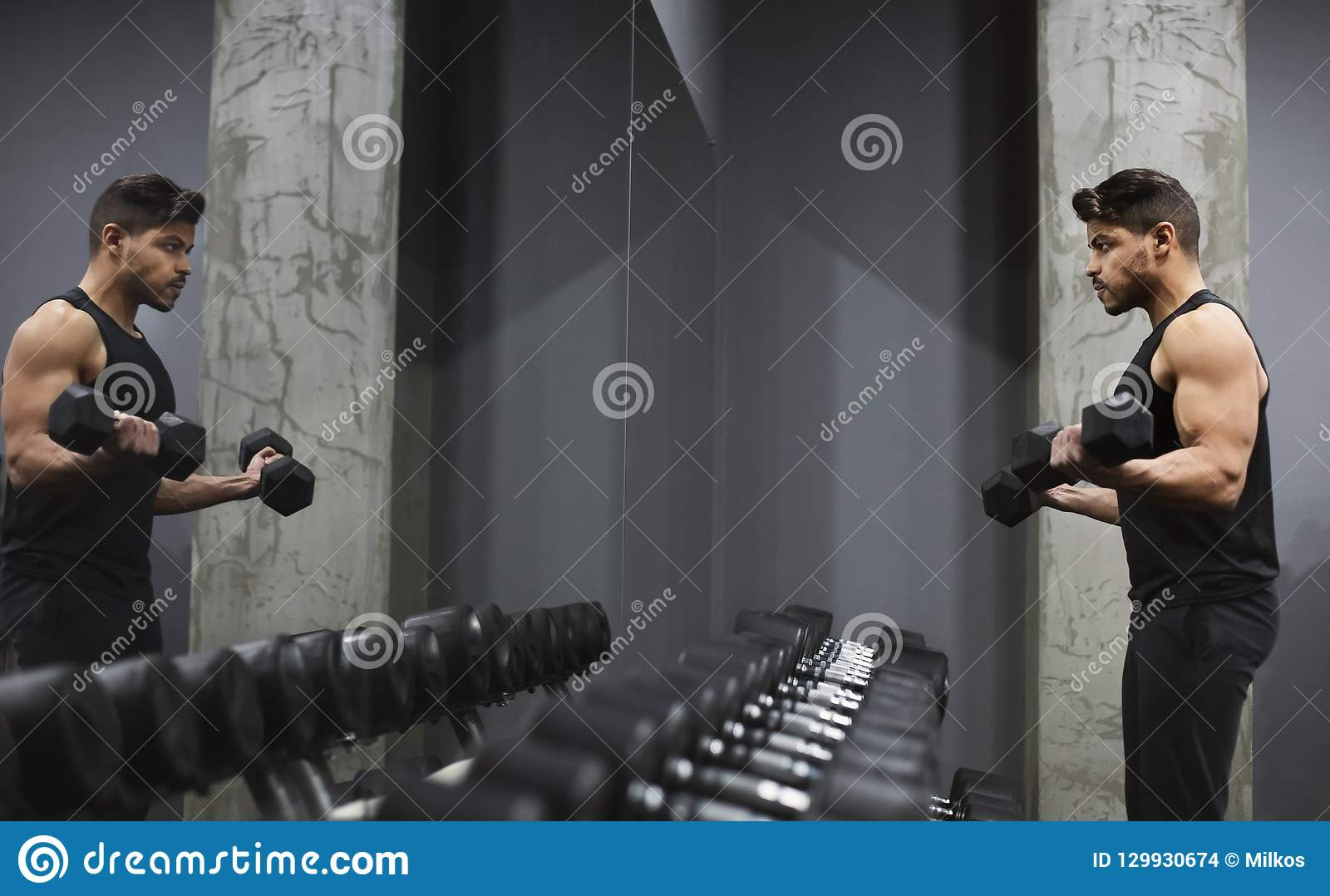 Dobrego przyglądającego młodego człowieka podnośni dumbbells przed lustrem