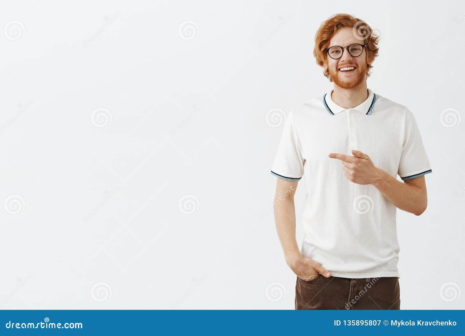 Dobroduszny seans my wielka oferta Portret życzliwy i szczęśliwy przystojny rudzielec samiec model w biały polo koszula wskazywać