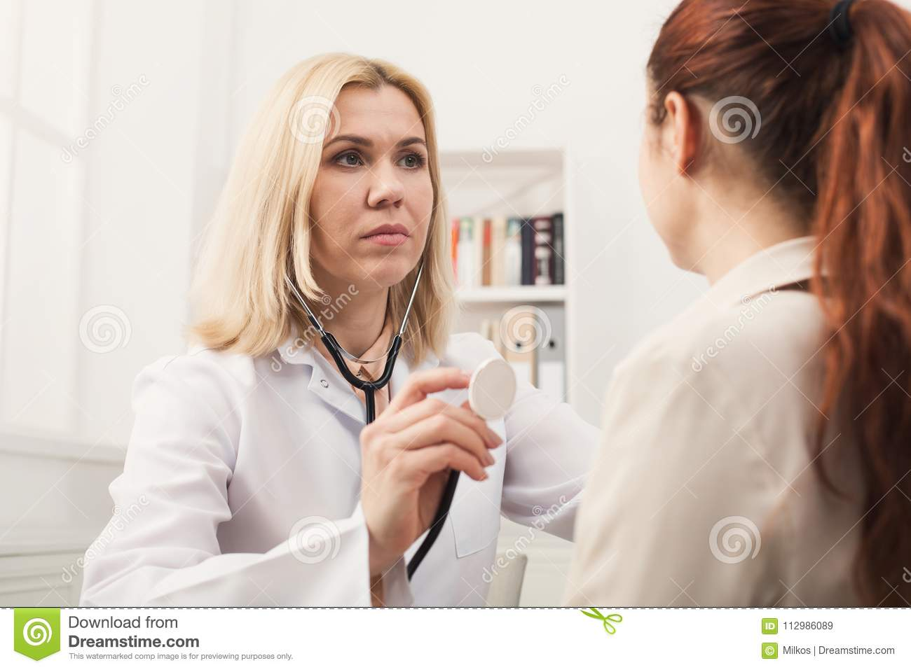 Doc with stethoscope checking patient heart beat