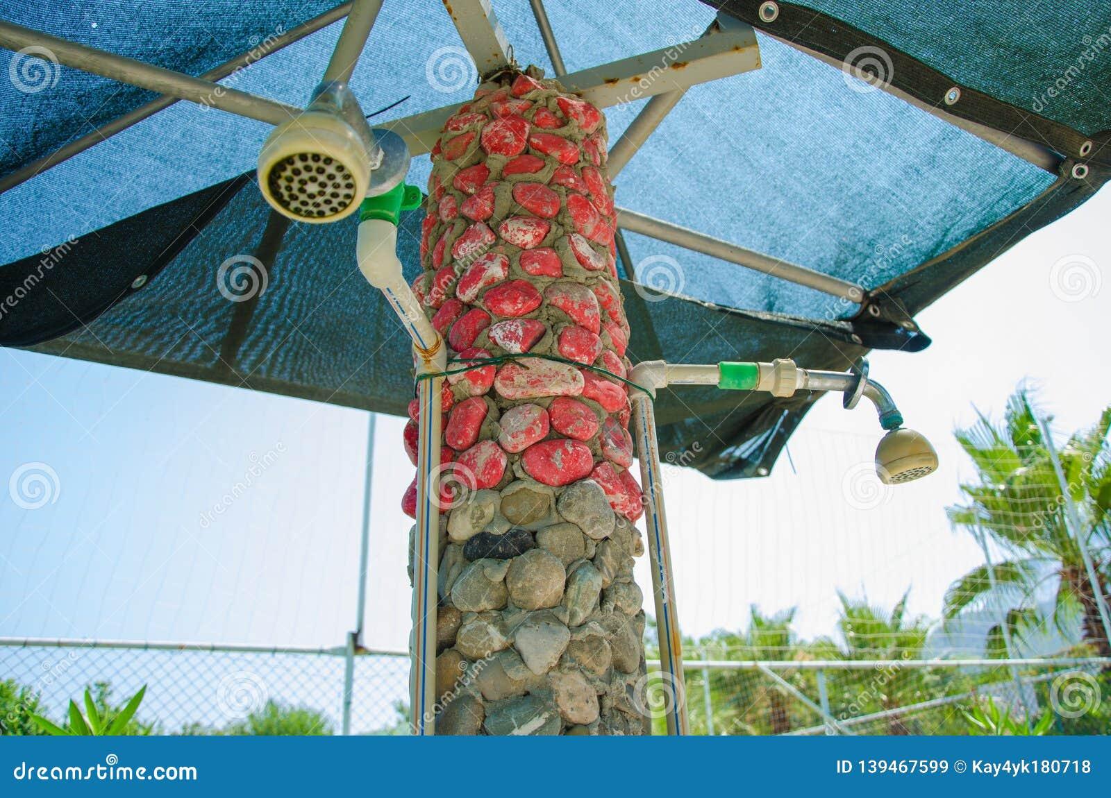 Doccia sulla via della pietra rossa sotto un ombrello blu vicino alla spiaggia