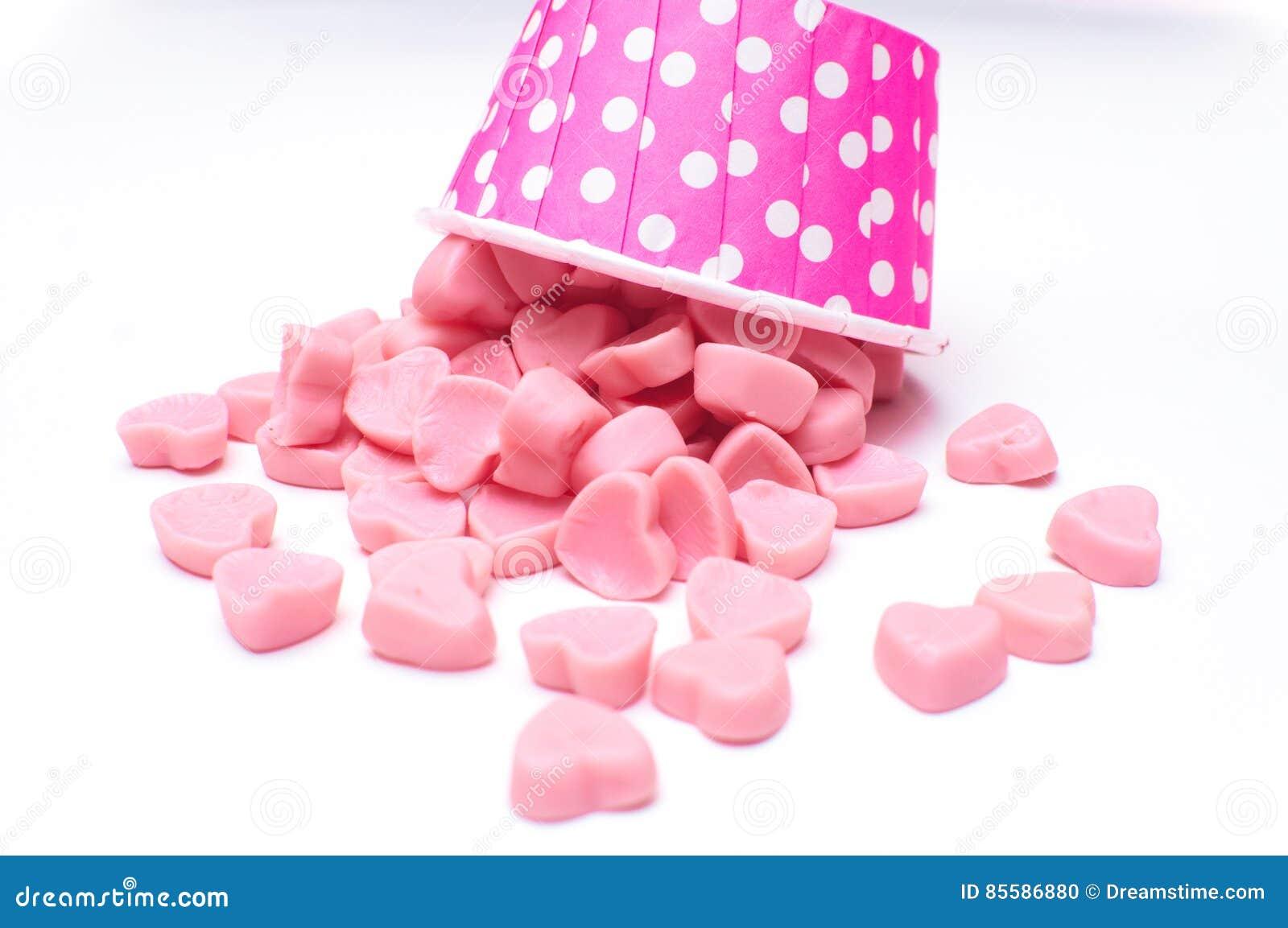 Doces de queda do coração nos copos de papel do às bolinhas cor-de-rosa isolados