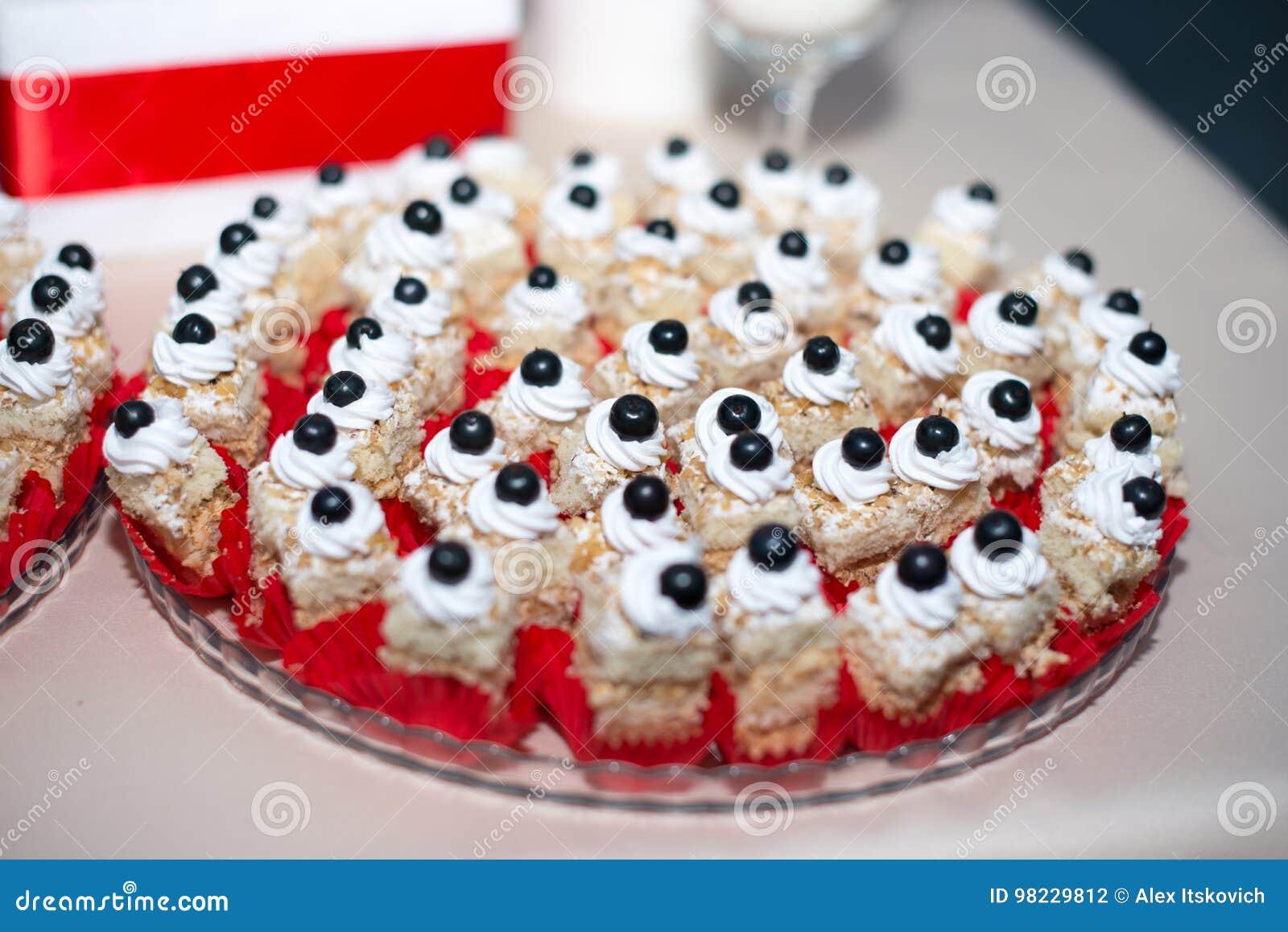 Doces deliciosos no bufete dos doces Lote de sobremesas coloridas na tabela