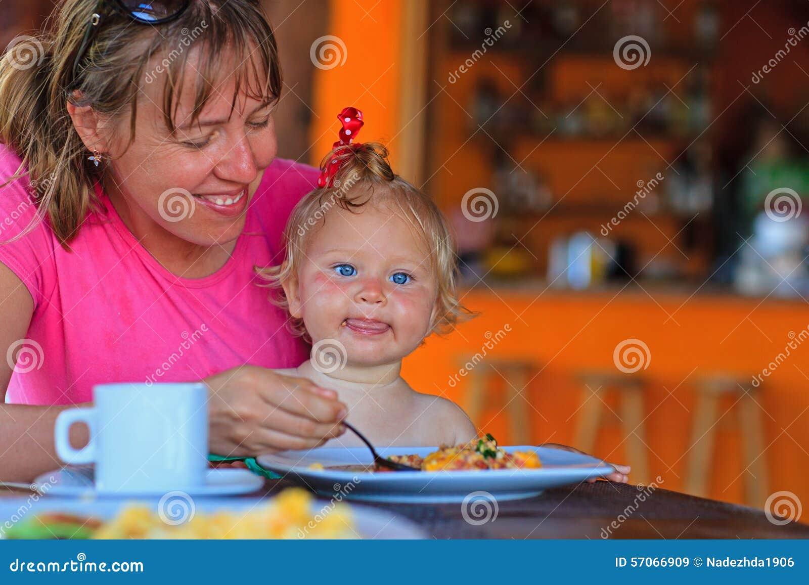 Dochter van de moeder de voedende zuigeling in koffie
