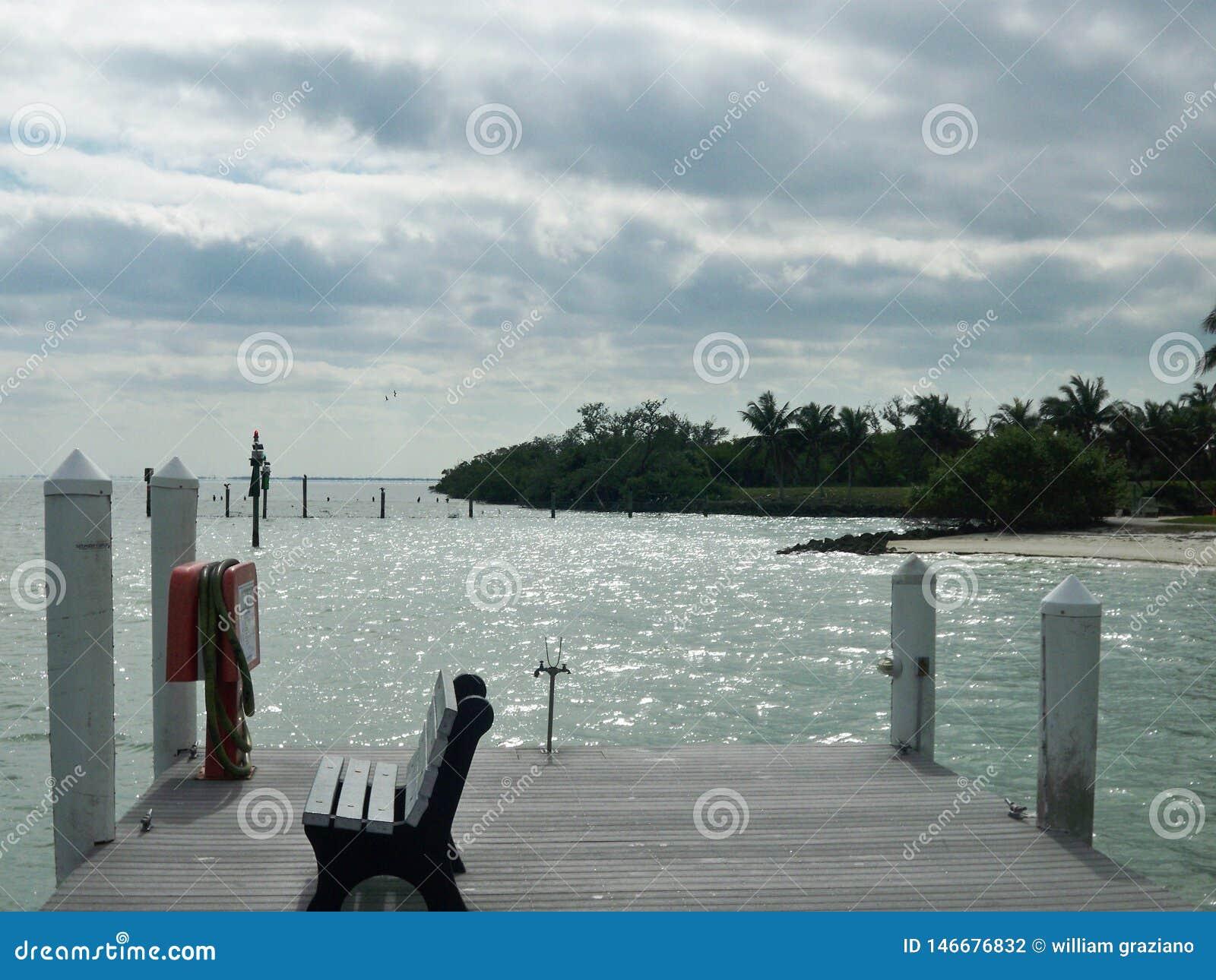 Dock avec de l eau de négligence banc un jour nuageux
