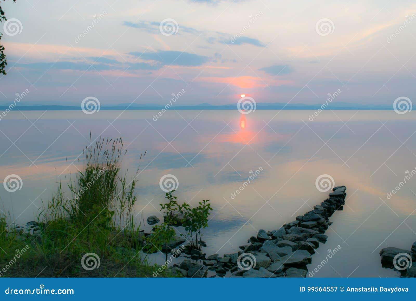 Dock en pierre romantique, passage couvert dans un lac à un coucher du soleil, Uveldy, les Monts Oural, Russie