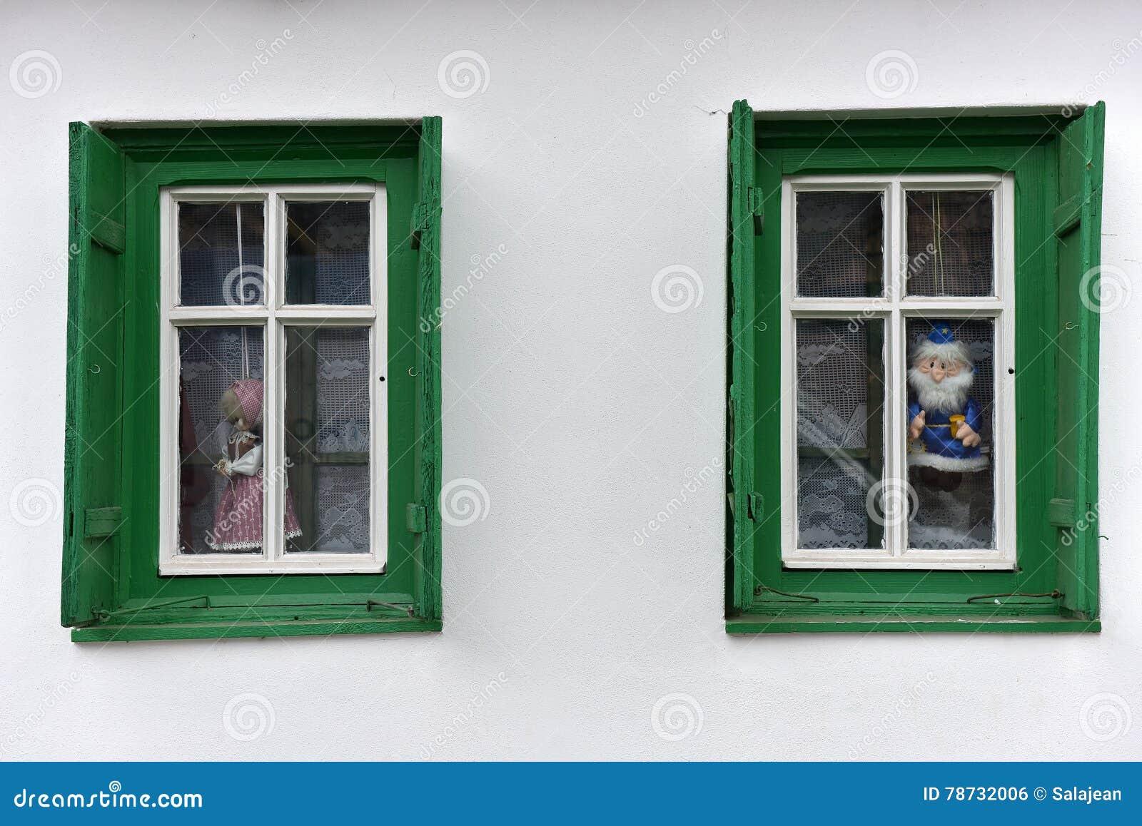 Dockor i fönstret i ett byhus