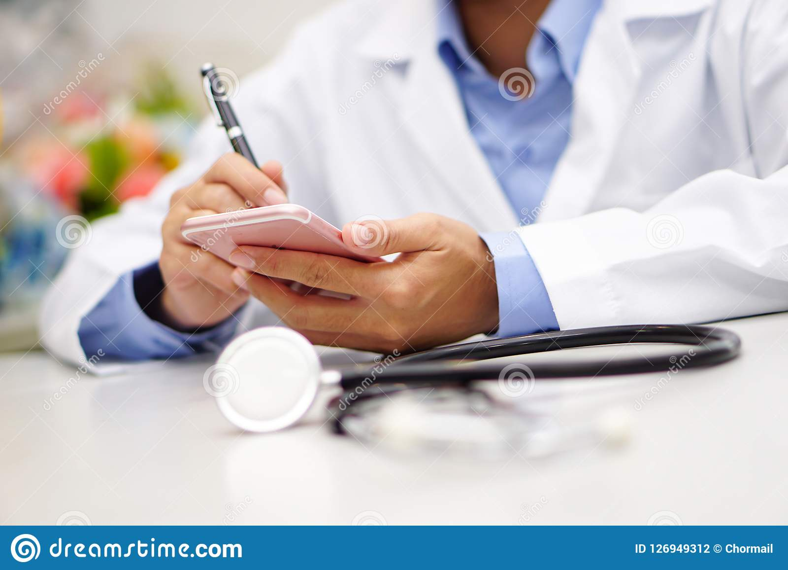 Docteur actif asiatique tenant le téléphone portable pour communiquer au sujet du travail à l hôpital