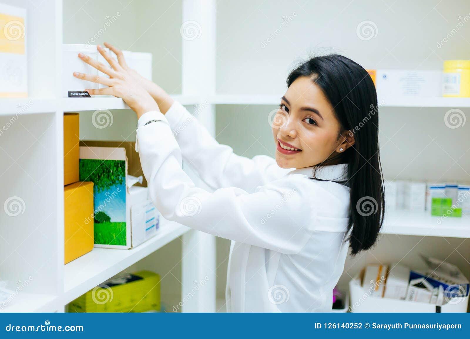 Docteur asiatique de pharmacien dans la robe blanche vérifiant les produits médicaux d actions de santé et travaillant dans la ph