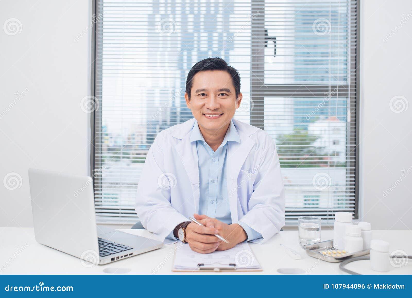 Docteur asiatique de sourire s asseyant à son bureau dans le bureau médical