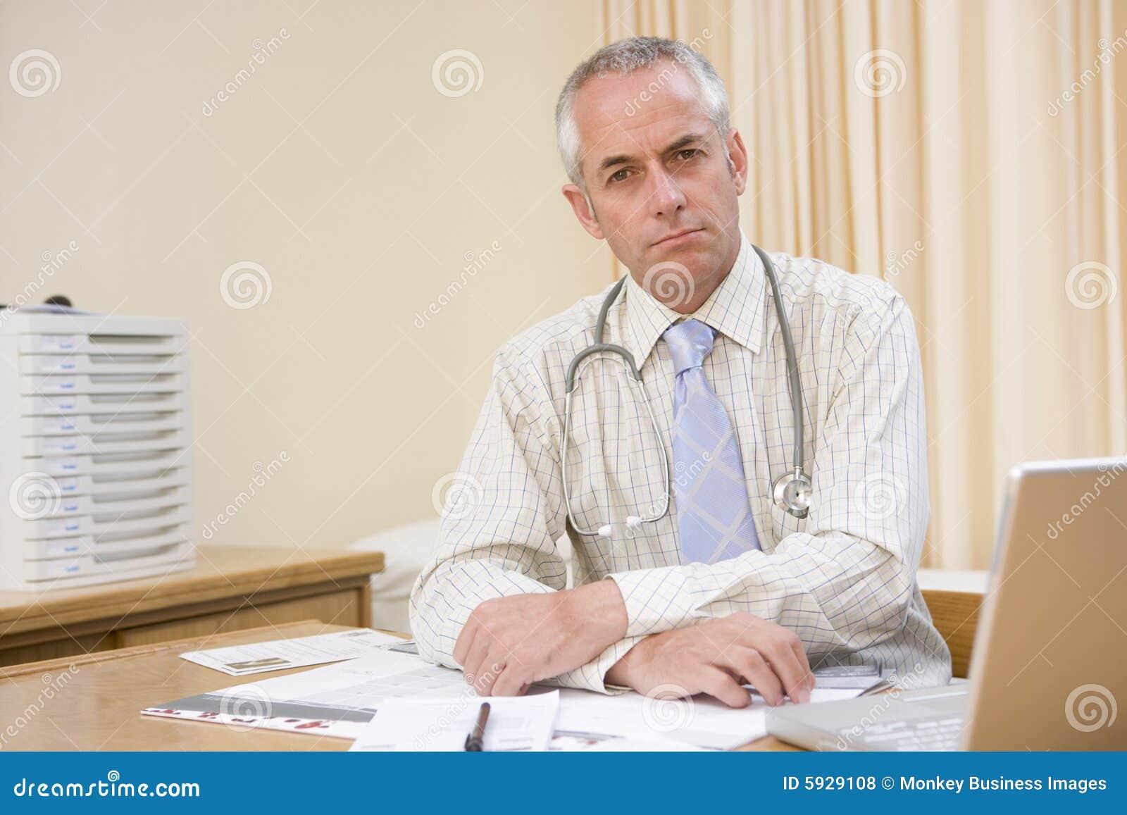 docteur avec l 39 ordinateur portatif dans le bureau du docteur photos libres de droits image. Black Bedroom Furniture Sets. Home Design Ideas