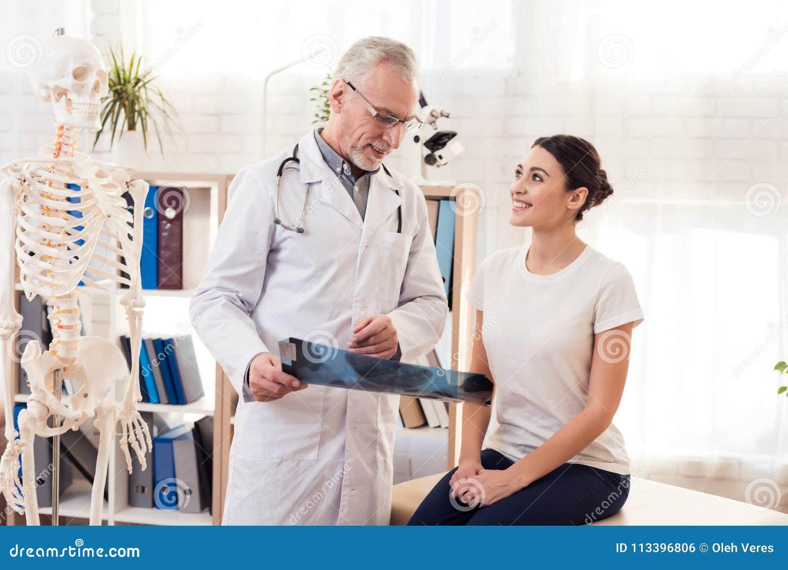 Docteur avec le stéthoscope et le patient féminin dans le bureau Le docteur montre le rayon X des hanches