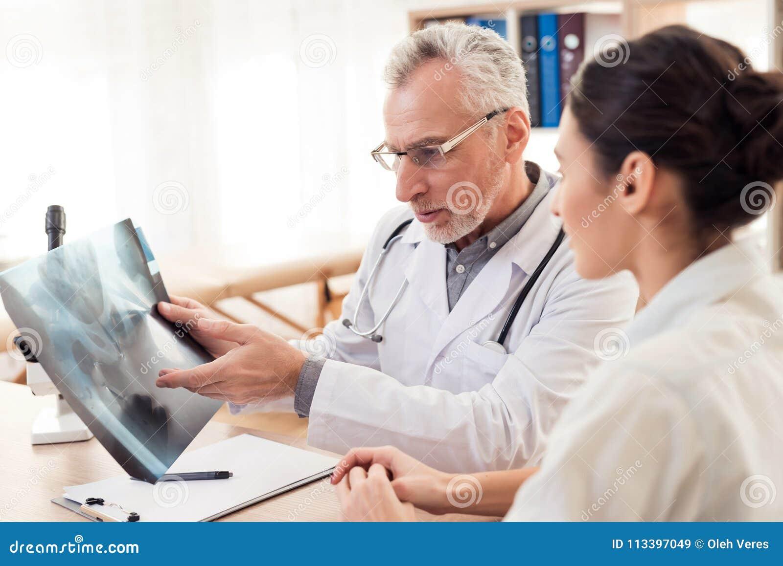 Docteur avec le stéthoscope et le patient féminin dans le bureau Le docteur montre le rayon X