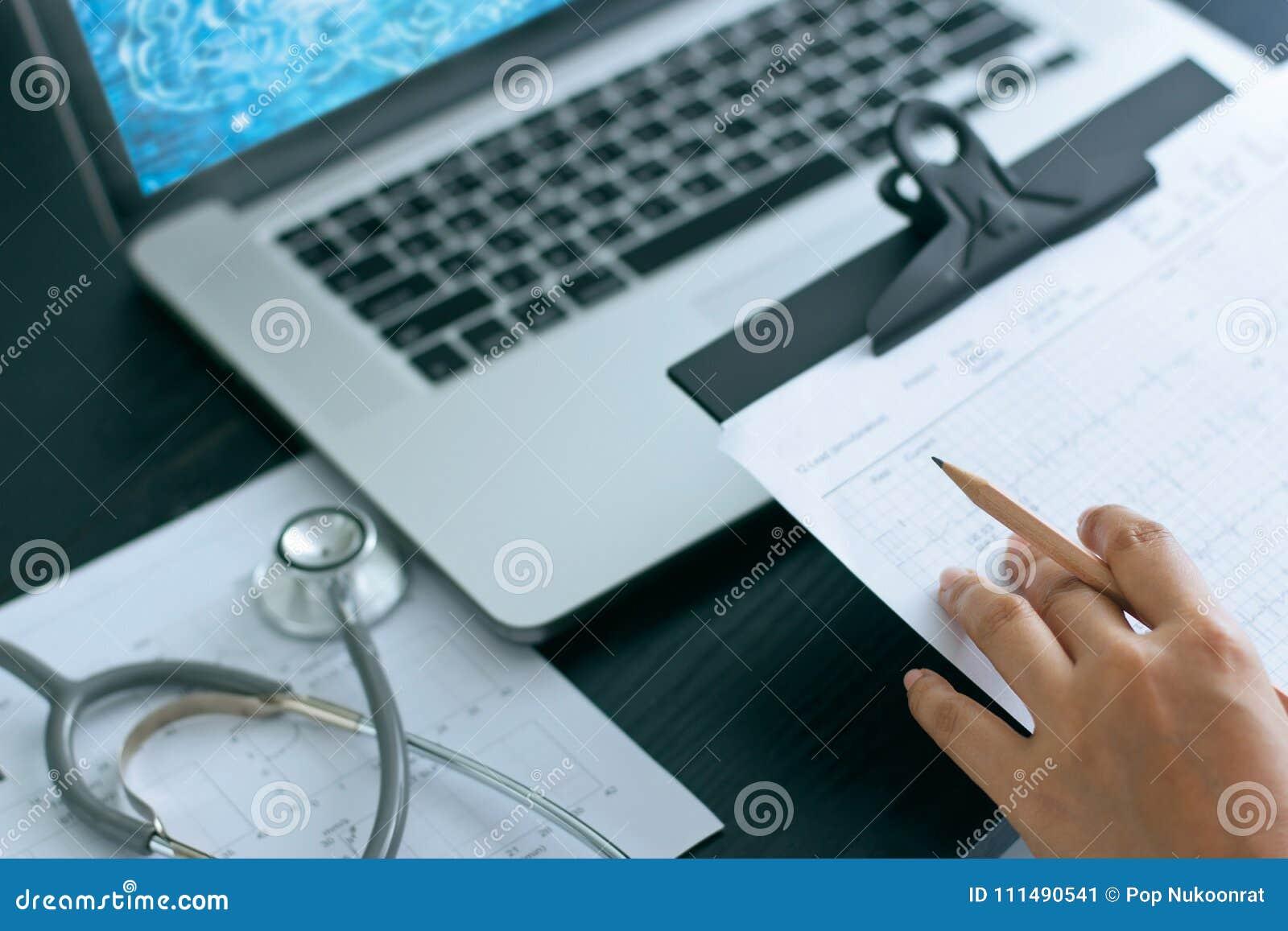Docteur avec le stéthoscope sur le diagramme de rapport, fonctionnant avec le labtop
