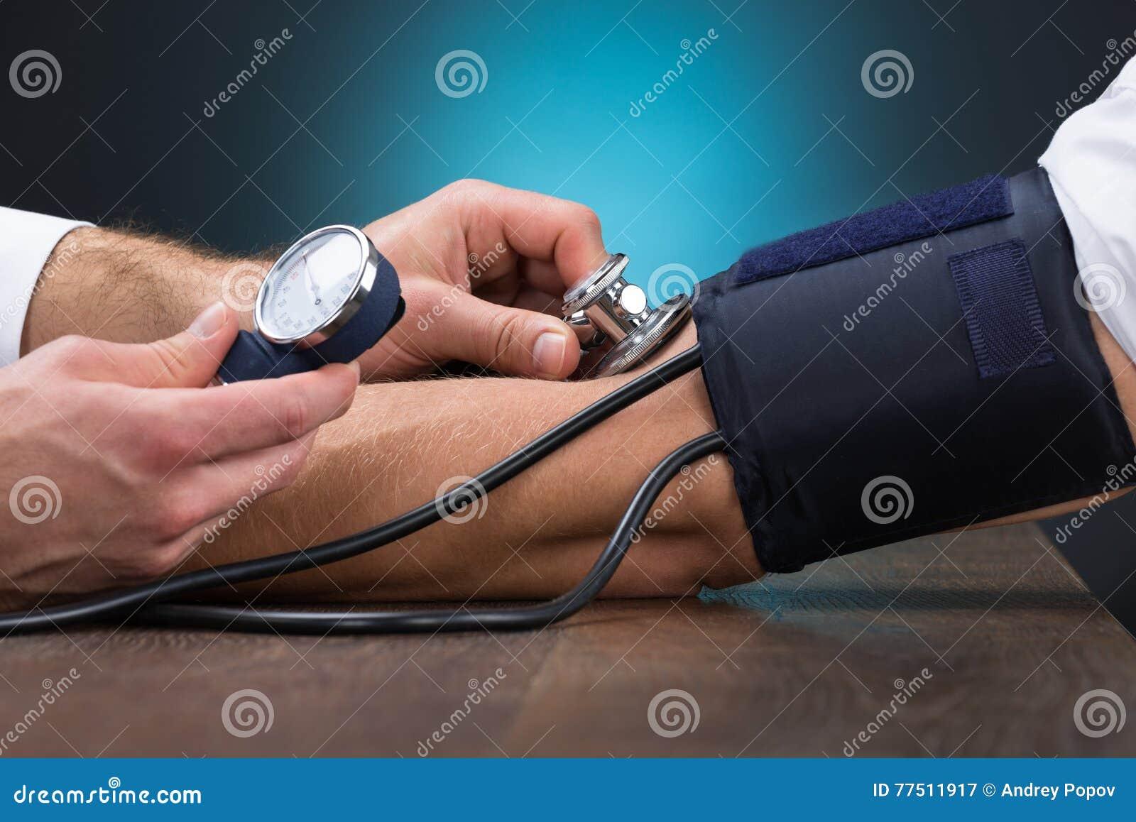 Docteur Checking Blood Pressure de patient au Tableau