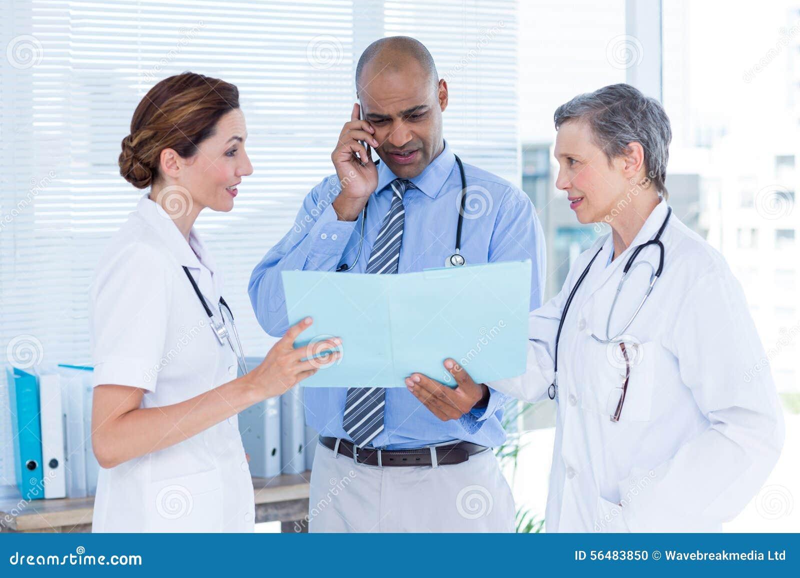 Docteur concentré montrant le dossier à ses collègues tout en appelant