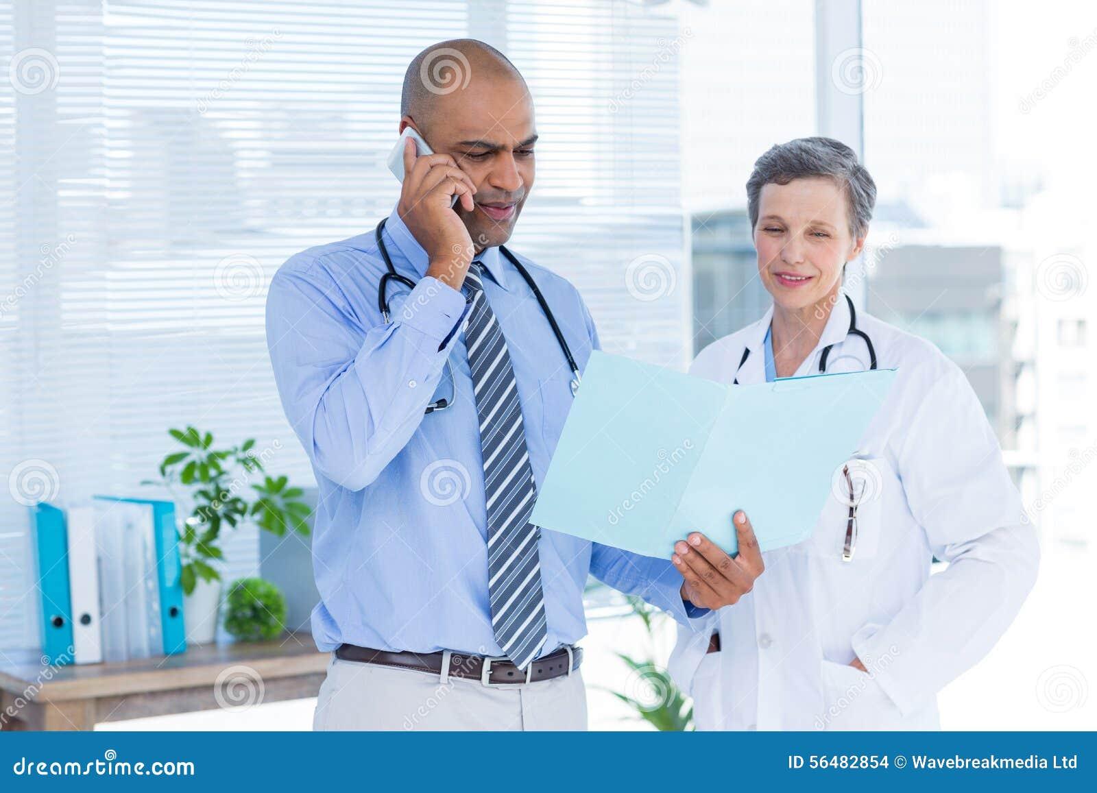Docteur concentré montrant le dossier à son collègue tout en appelant