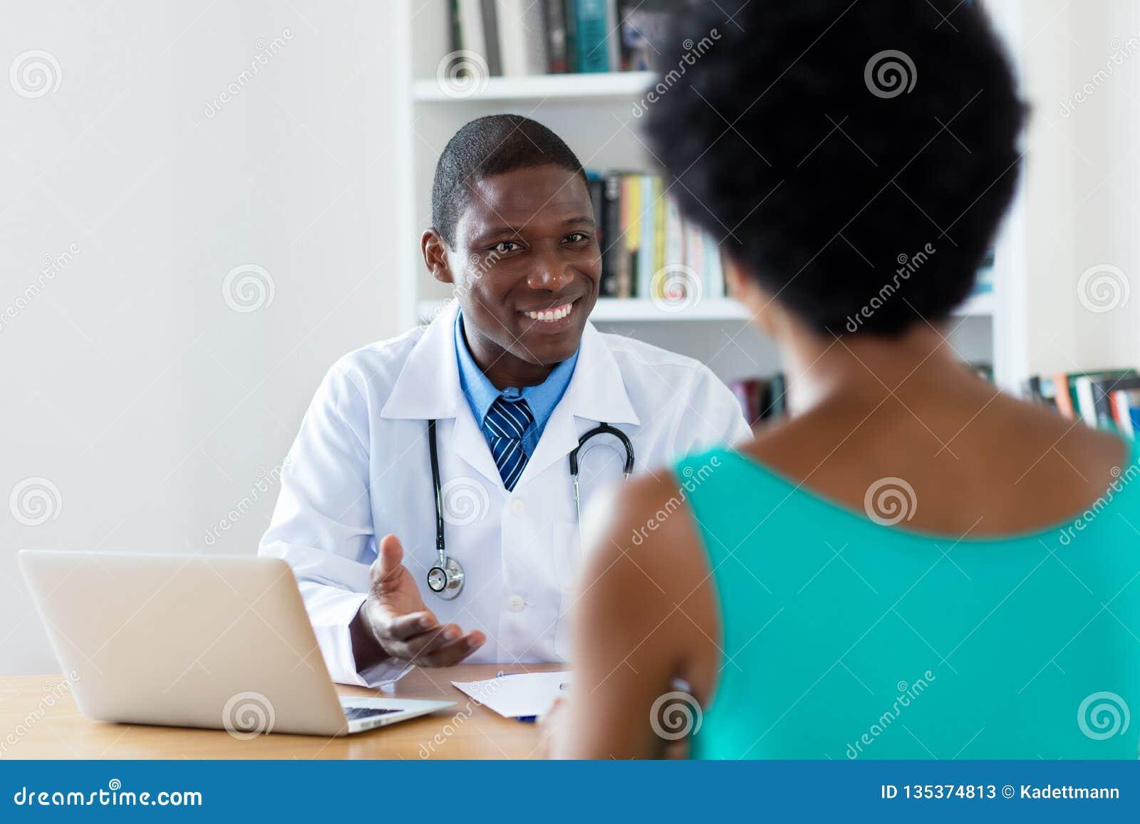 Docteur d afro-américain avec de bonnes nouvelles pour le patient féminin