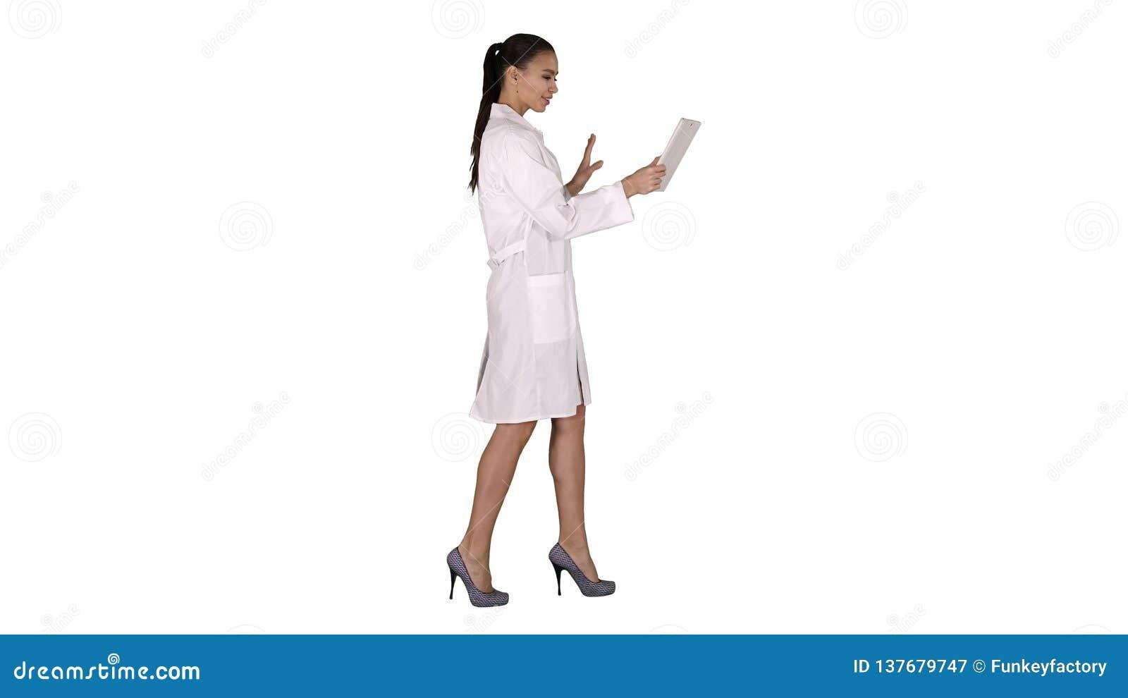 Docteur de jeune femme tenant le comprimé dans des ses mains et faisant l appel visuel sur le fond blanc