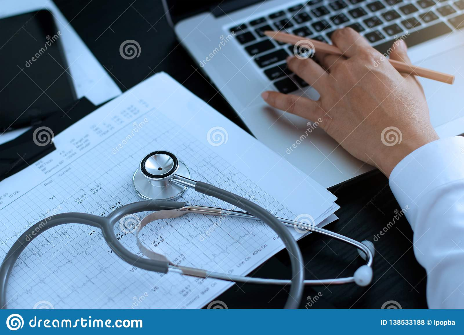 Docteur de médecine Stéthoscope avec le rapport de battement de coeur, analysant le contrôle sur l ordinateur portable