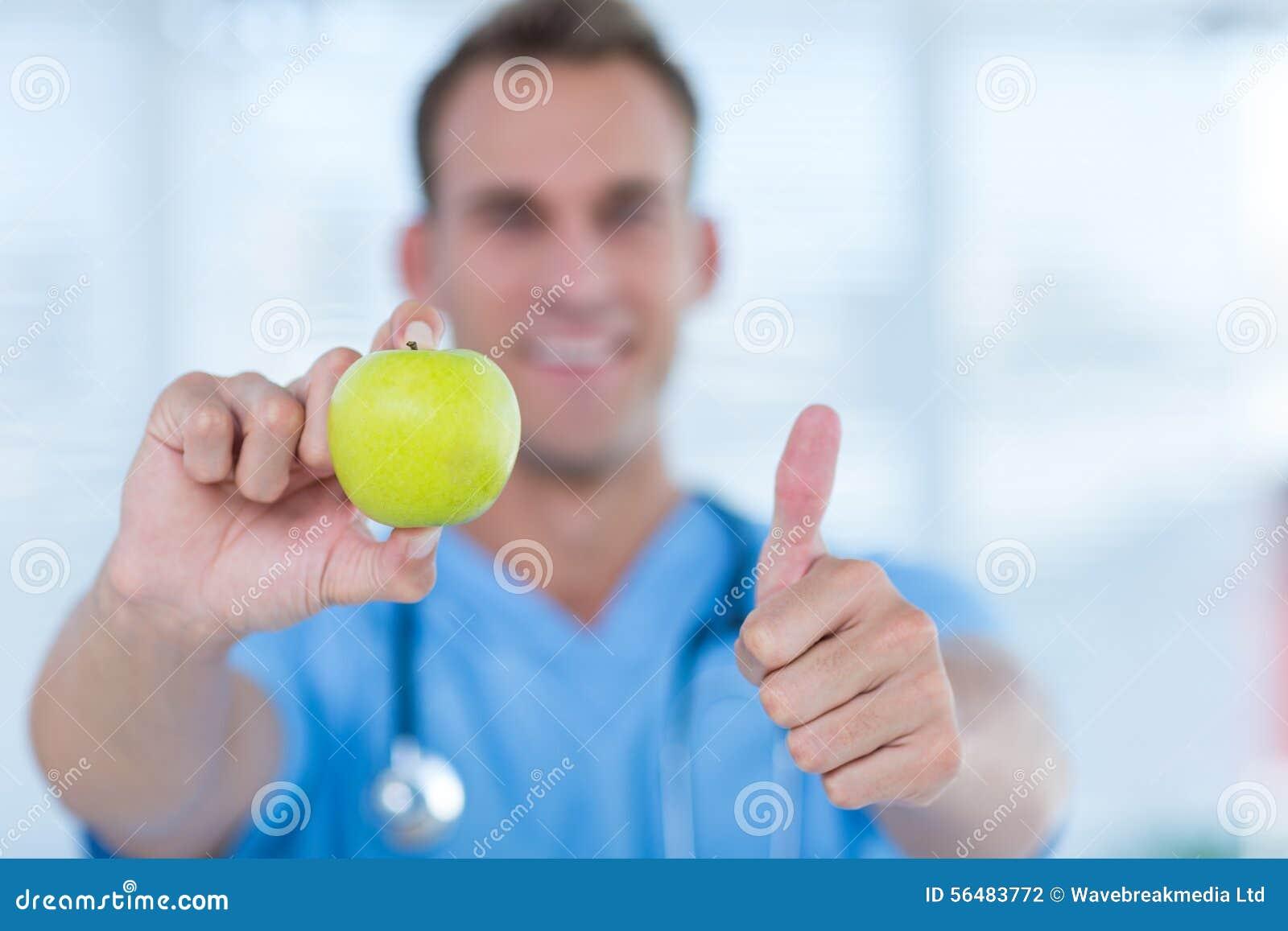 Docteur de sourire présent une pomme verte