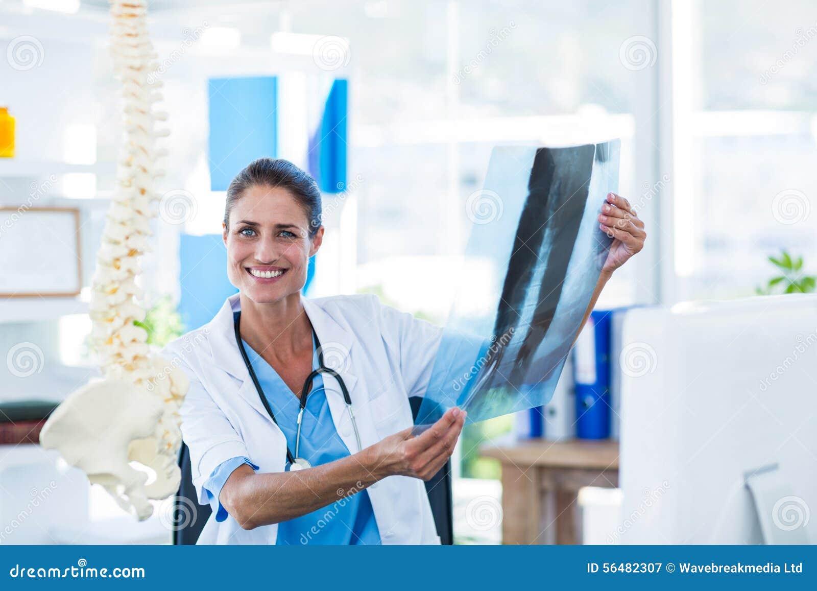 Docteur de sourire regardant des rayons X
