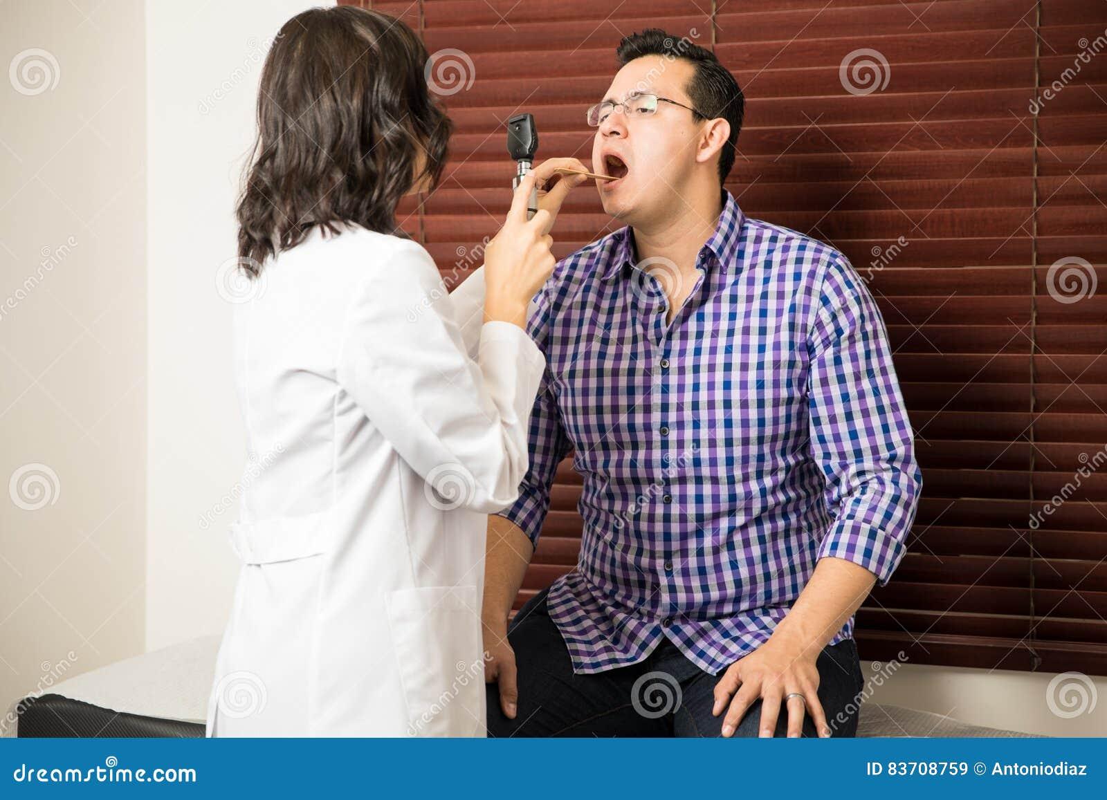Docteur examinant la gorge patiente du ` s