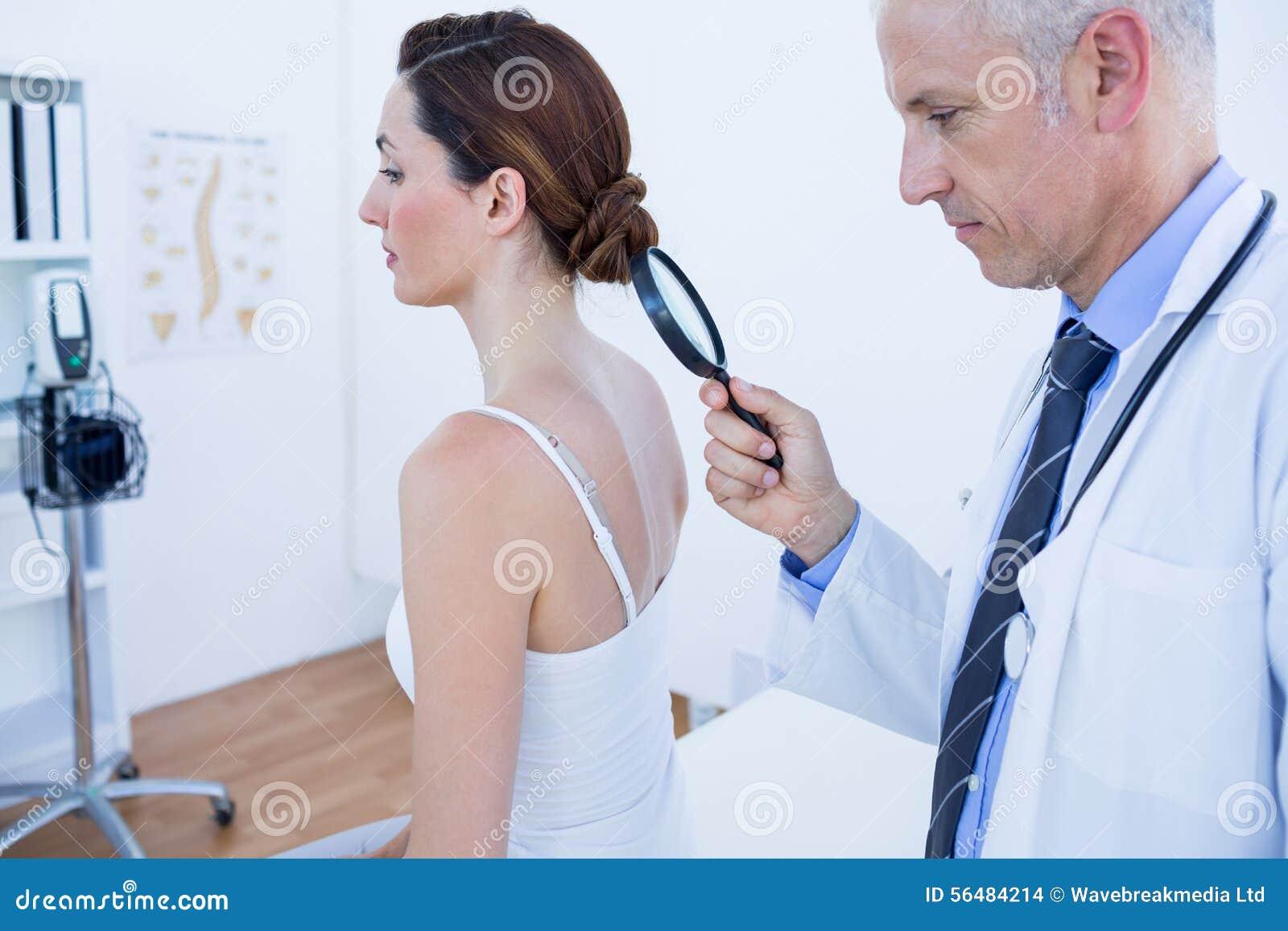 Docteur examinant son dos de patient avec la loupe