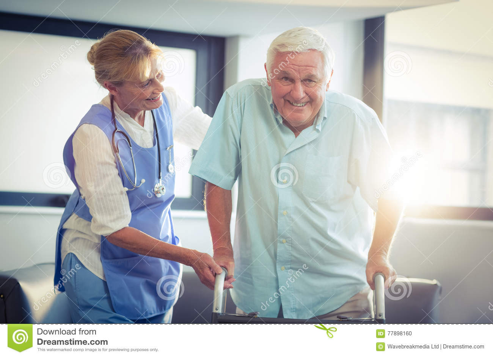Docteur féminin aidant l homme supérieur à marcher avec le marcheur