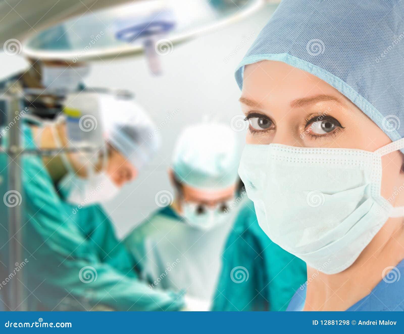 Docteur féminin avec l équipe chirurgicale