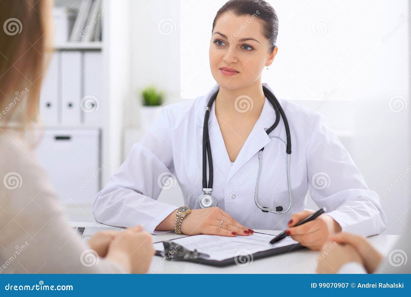 Docteur féminin de brune parlant au patient dans le bureau d