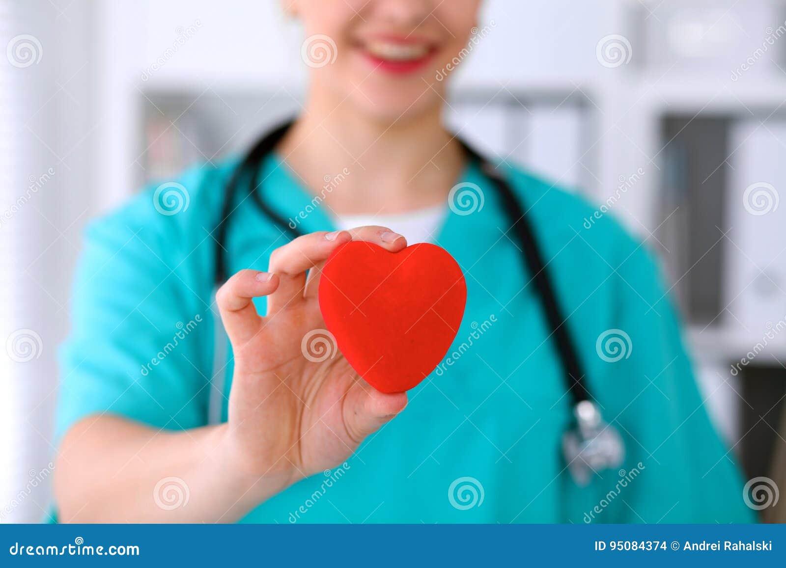 Docteur féminin de chirurgien avec le stéthoscope tenant le coeur