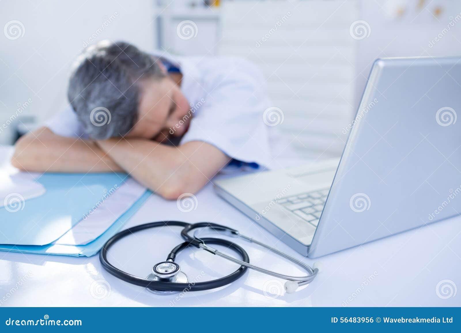 Docteur féminin dormant sur le bureau