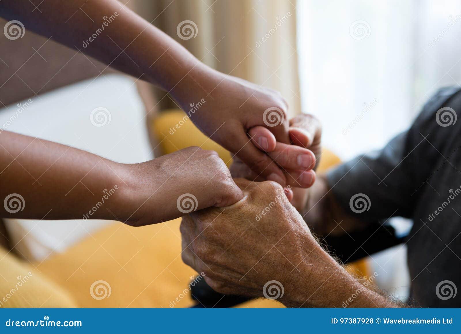 Docteur féminin et homme supérieur tenant des mains dans la maison de repos