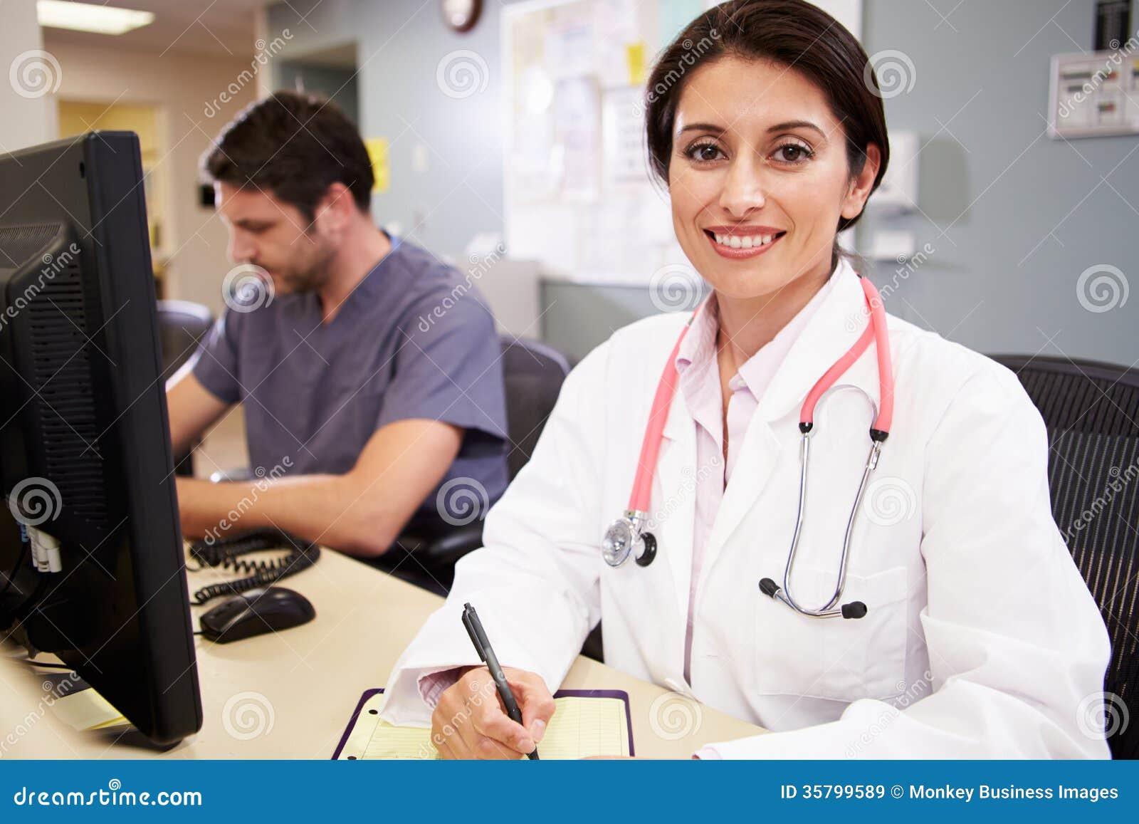 Docteur féminin With Male Nurse travaillant à la station d infirmières