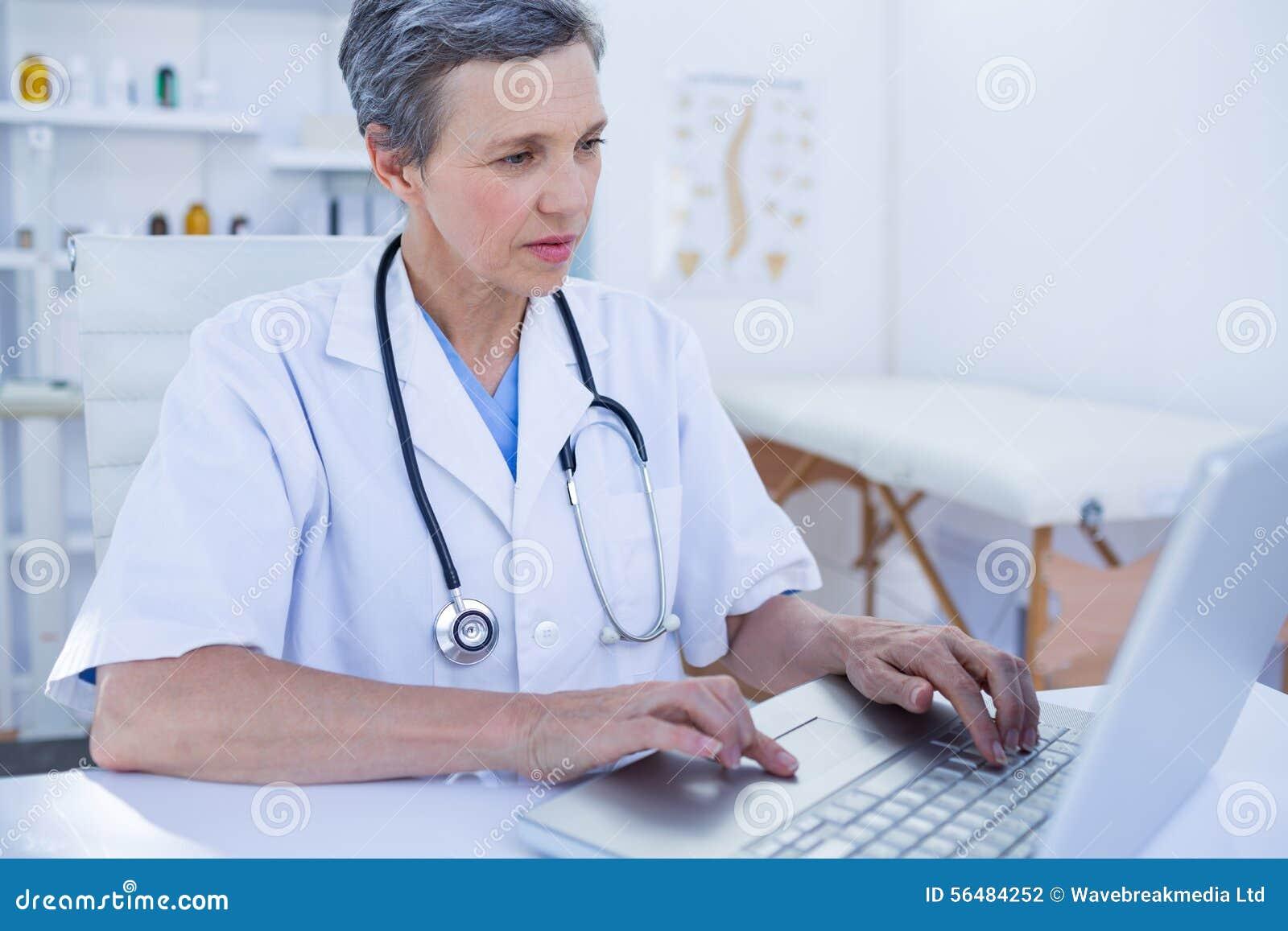 Docteur féminin sérieux à l aide de son ordinateur portable