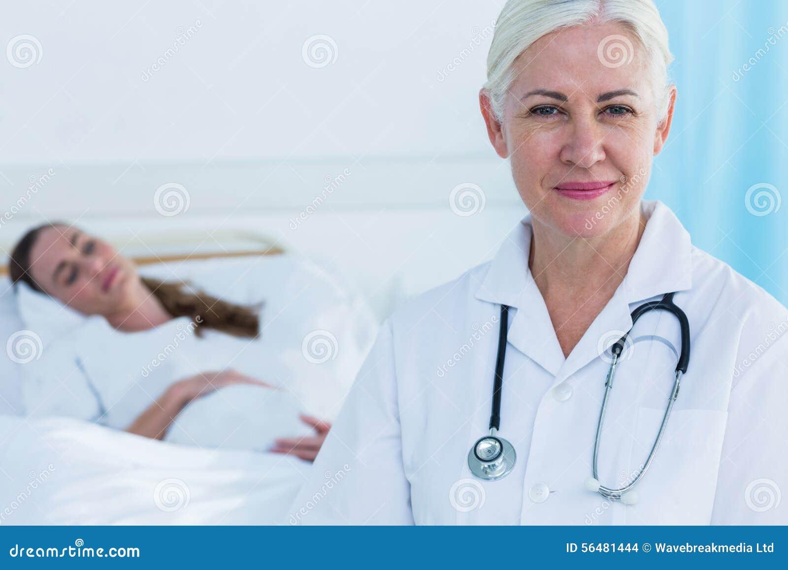 Docteur féminin souriant à l appareil-photo tandis que son sommeil patient