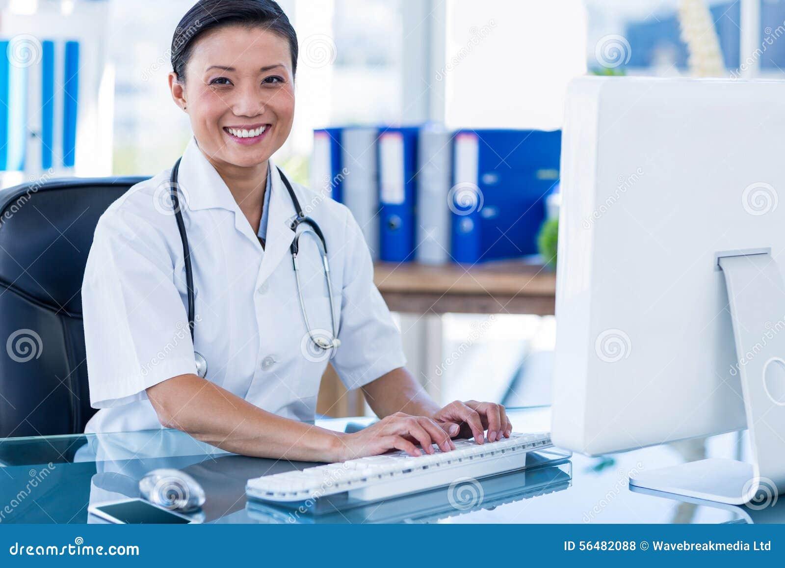 Docteur heureux à l aide de son ordinateur et regardant l appareil-photo