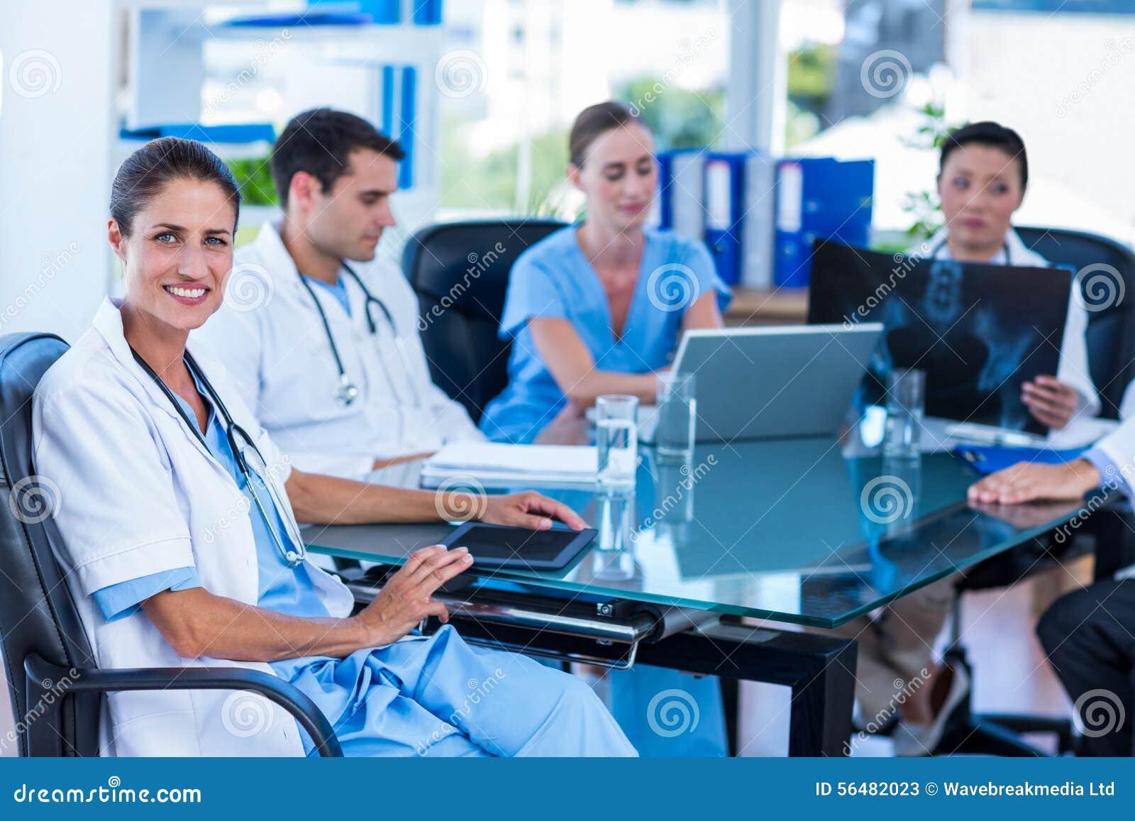 Docteur heureux regardant l appareil-photo avec des collègues derrière