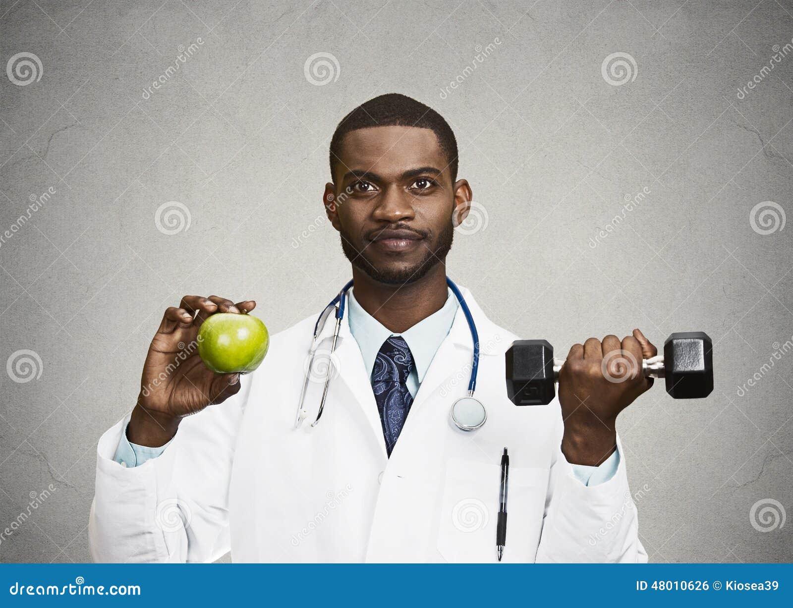 Docteur heureux tenant la pomme verte, haltère