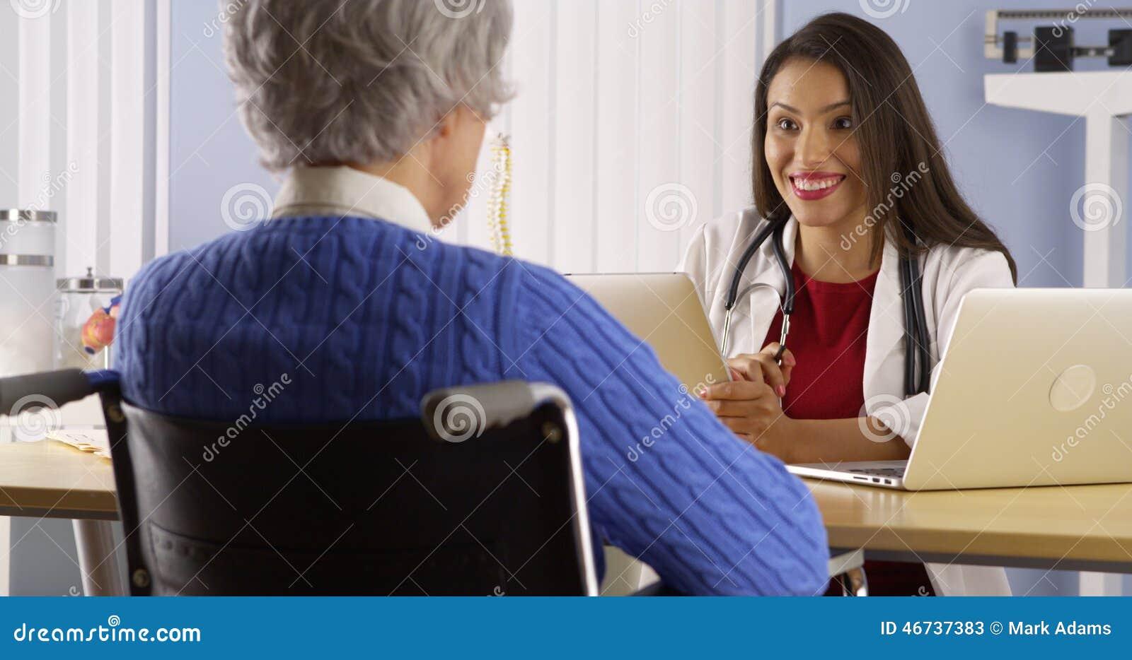 Docteur hispanique de femme parlant avec le patient plus âgé
