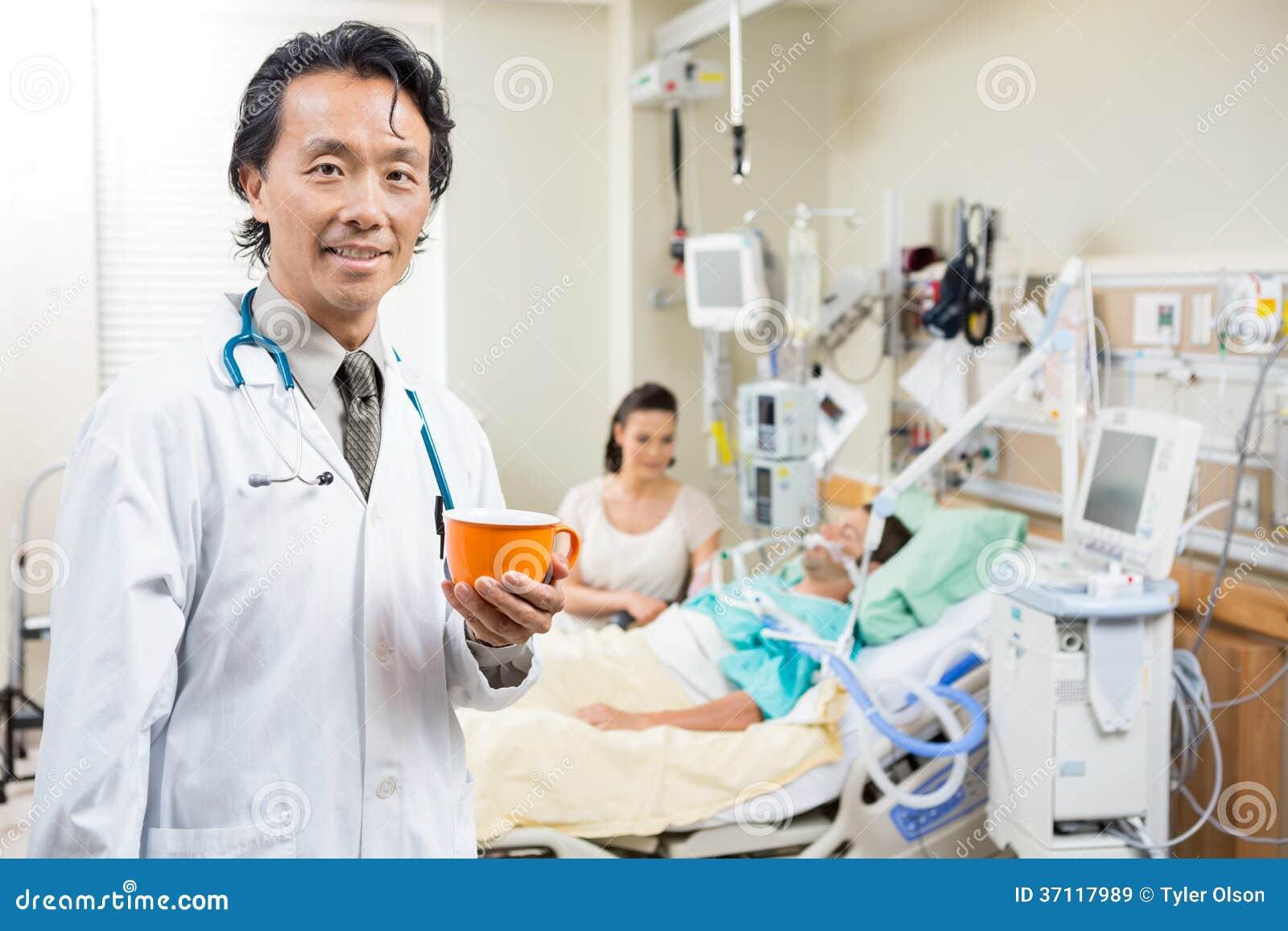 Docteur Holding Coffee Cup avec le patient se reposant dessus